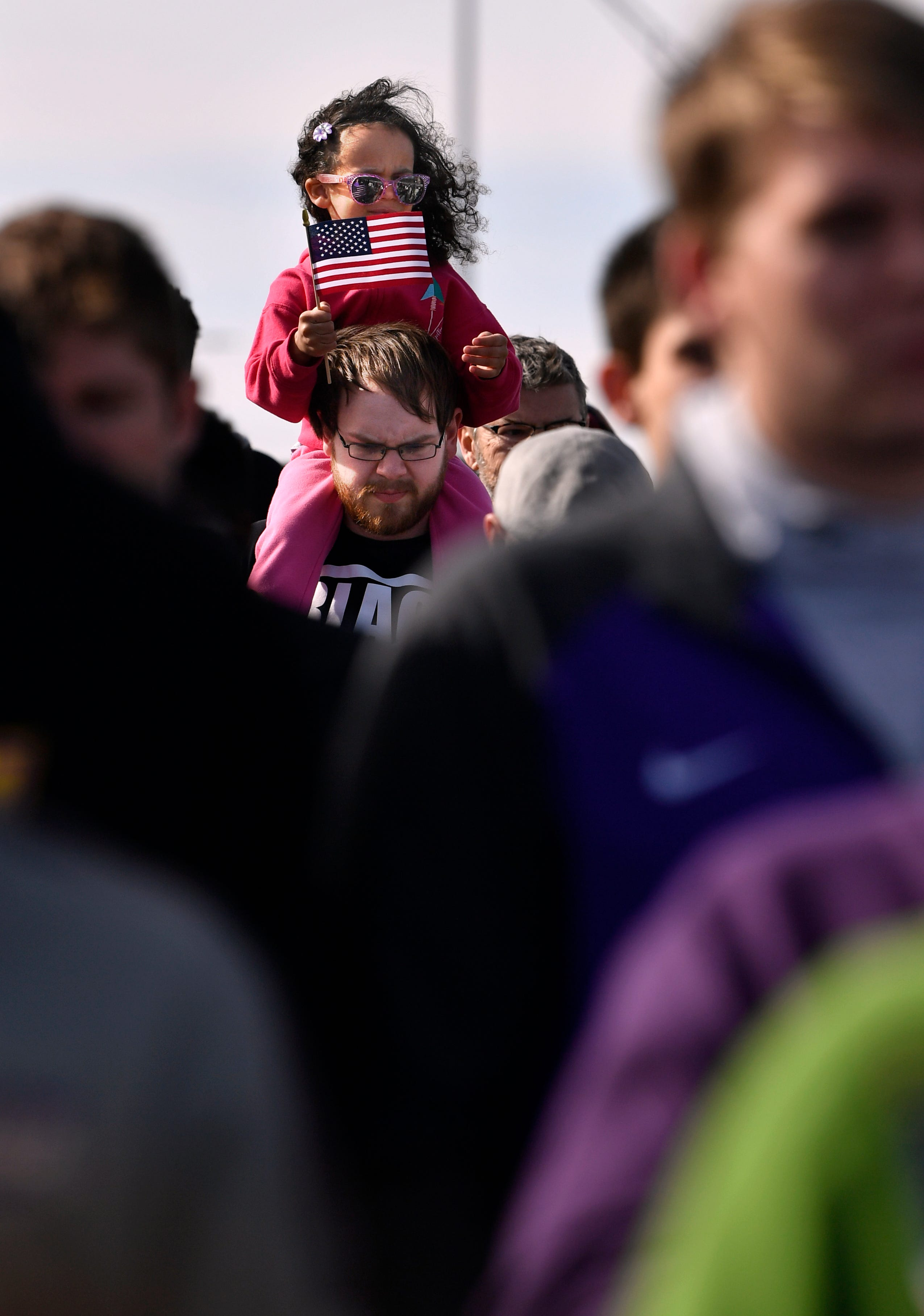 Josh Blasingame carries his daughter Amelia, 4, on his shoulders during Monday's Martin Luther King Jr. march on East Highway 80 in Abilene. About 1,000 gathered to honor King's legacy.