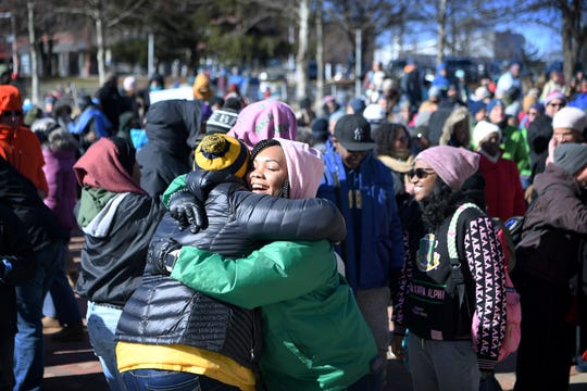 Patricia Mathes gives a hug at the instruction of a speaker during the Dr. Martin Luther King, Jr. Peace March and Rally at Pack Square Park Monday.
