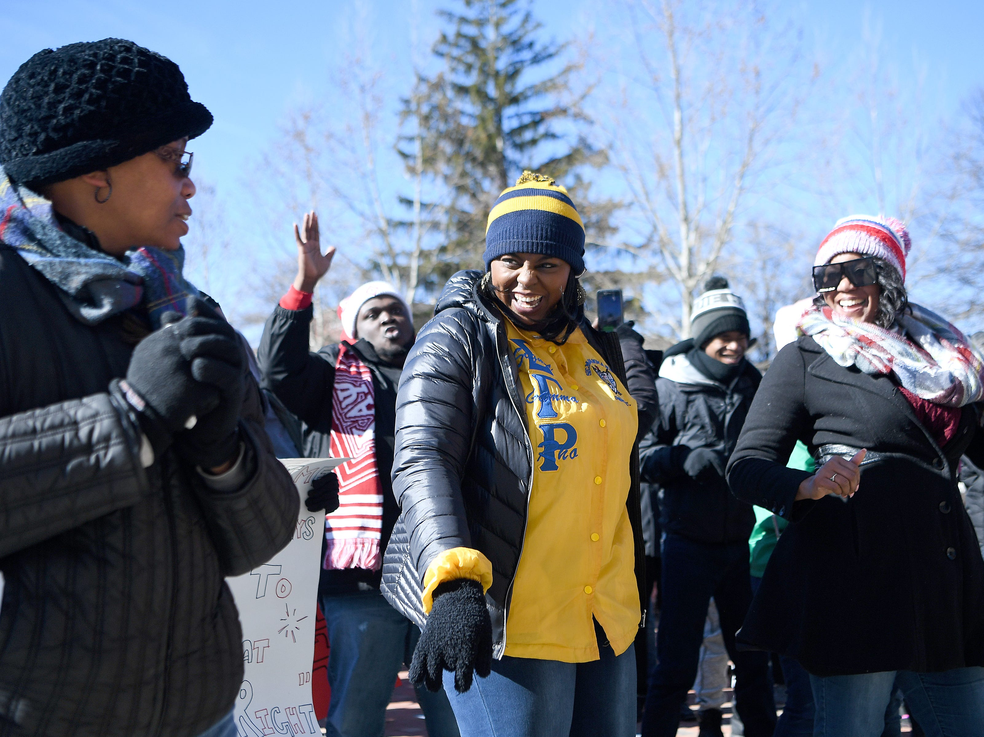 Alexis Wardlow, center, and Elizabeth Garland, right, do the Electric Slide during the Dr. Martin Luther King, Jr. Peace March and Rally at Pack Square Park on Jan. 21, 2019.
