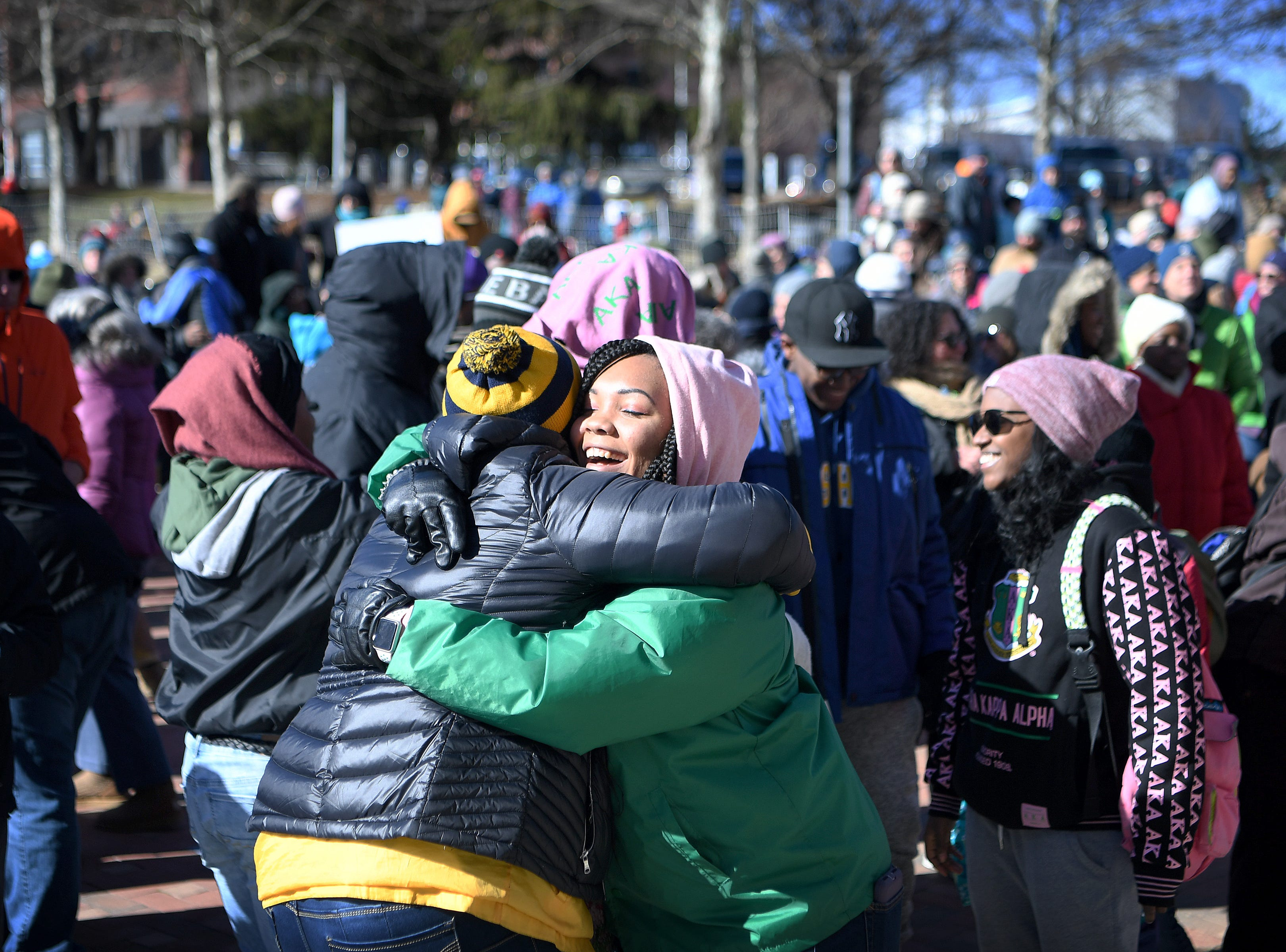 Patricia Mathes gives out a hug at the instruction of the speaker during the Dr. Martin Luther King, Jr. Peace March and Rally at Pack Square Park on Jan. 21, 2019.