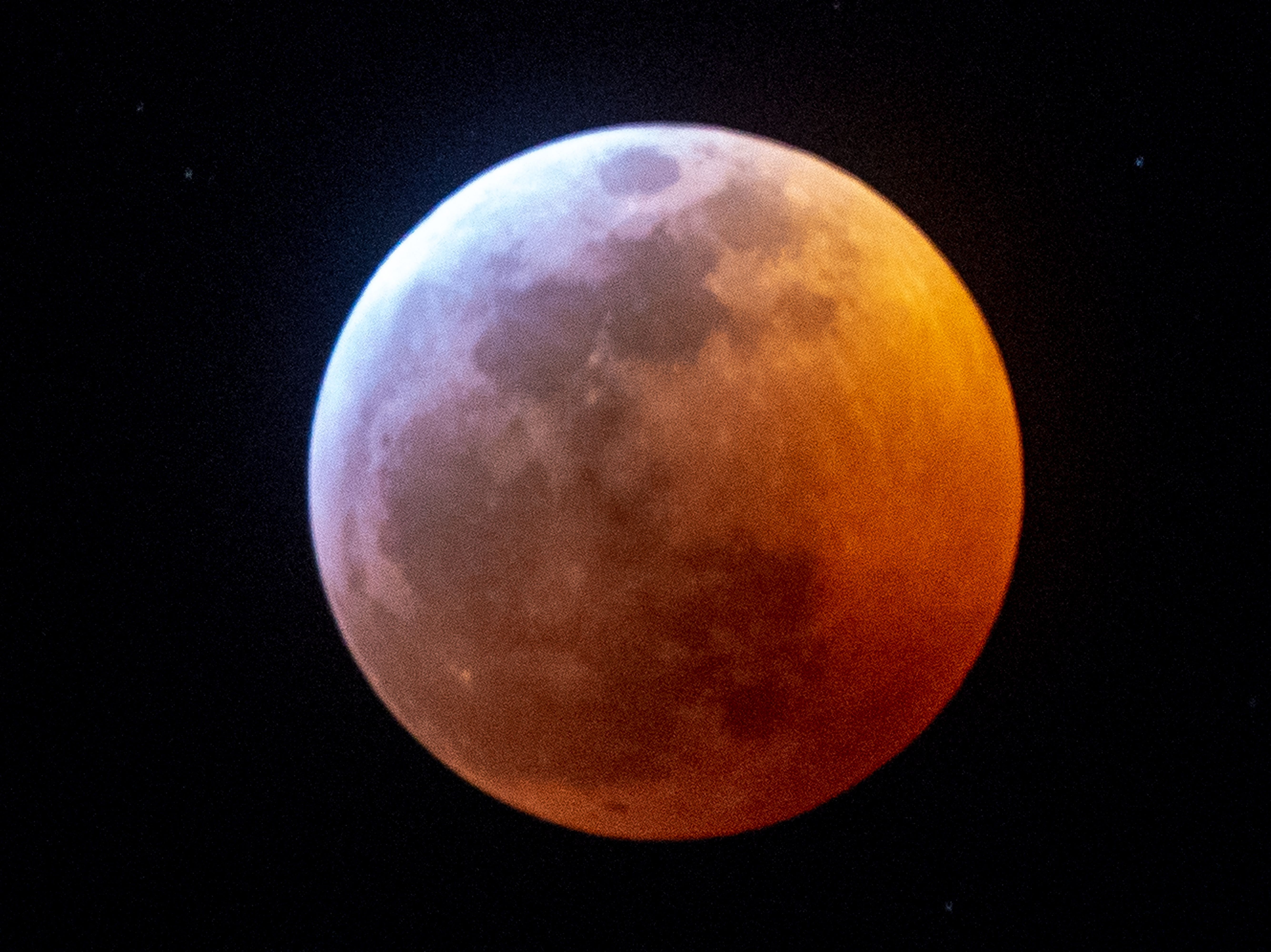 Earth's shadow almost totally obscures the view of the so-called Super Blood Wolf Moon during a total lunar eclipse, on Sunday January 20, 2019, in Miami, Florida. - The January 21 total lunar eclipse will be the last one until May 2021, and the last one visible from the United States until 2022. (Photo by Gaston De Cardenas / AFP)
