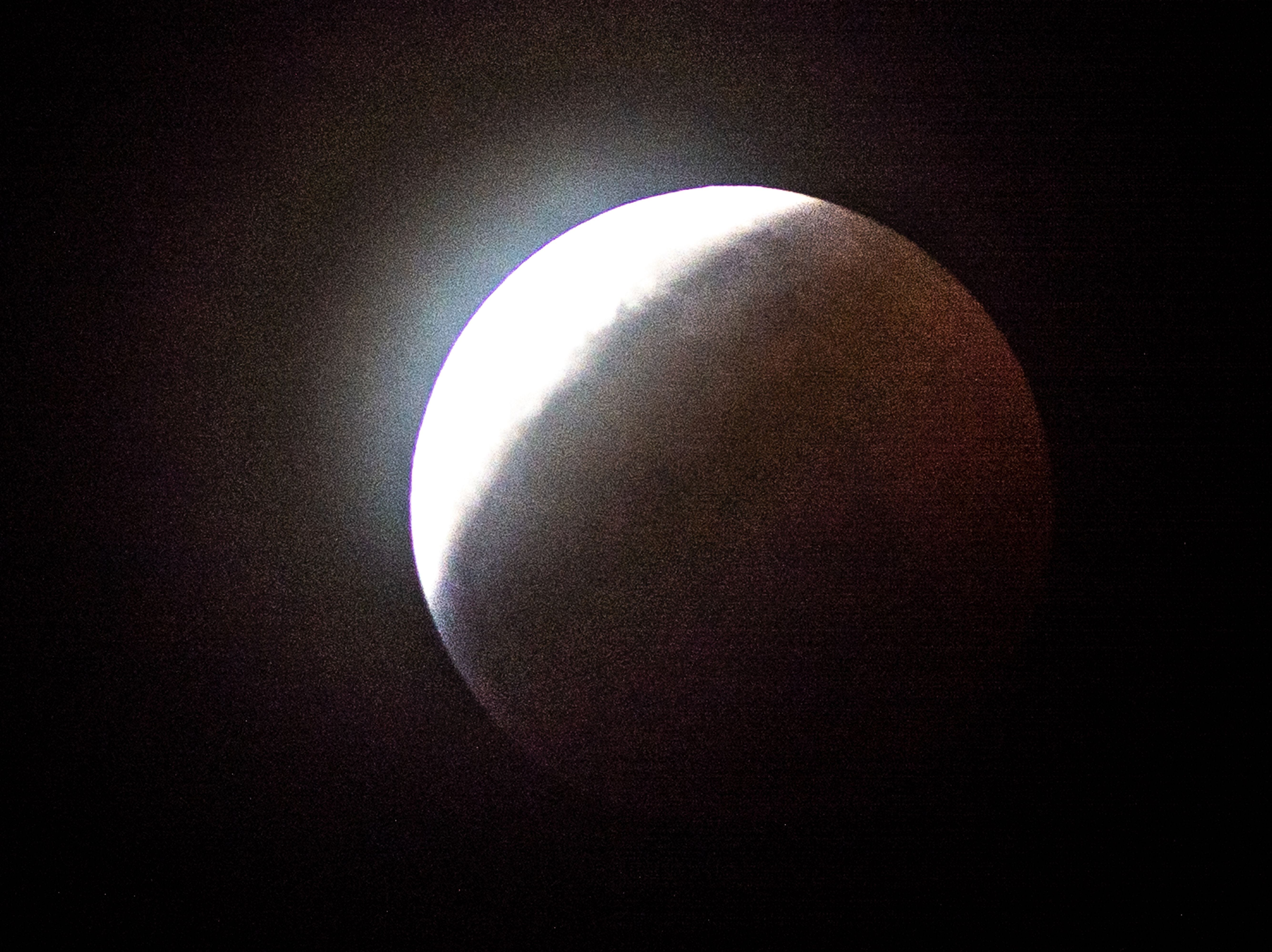 Earth's shadow begins to totally obscure the view of the so-called Super Blood Wolf Moon during a total lunar eclipse, on Sunday January 20, 2019, in Miami, Florida. - The January 21 total lunar eclipse will be the last one until May 2021, and the last one visible from the United States until 2022. (Photo by Gaston De Cardenas / AFP)
