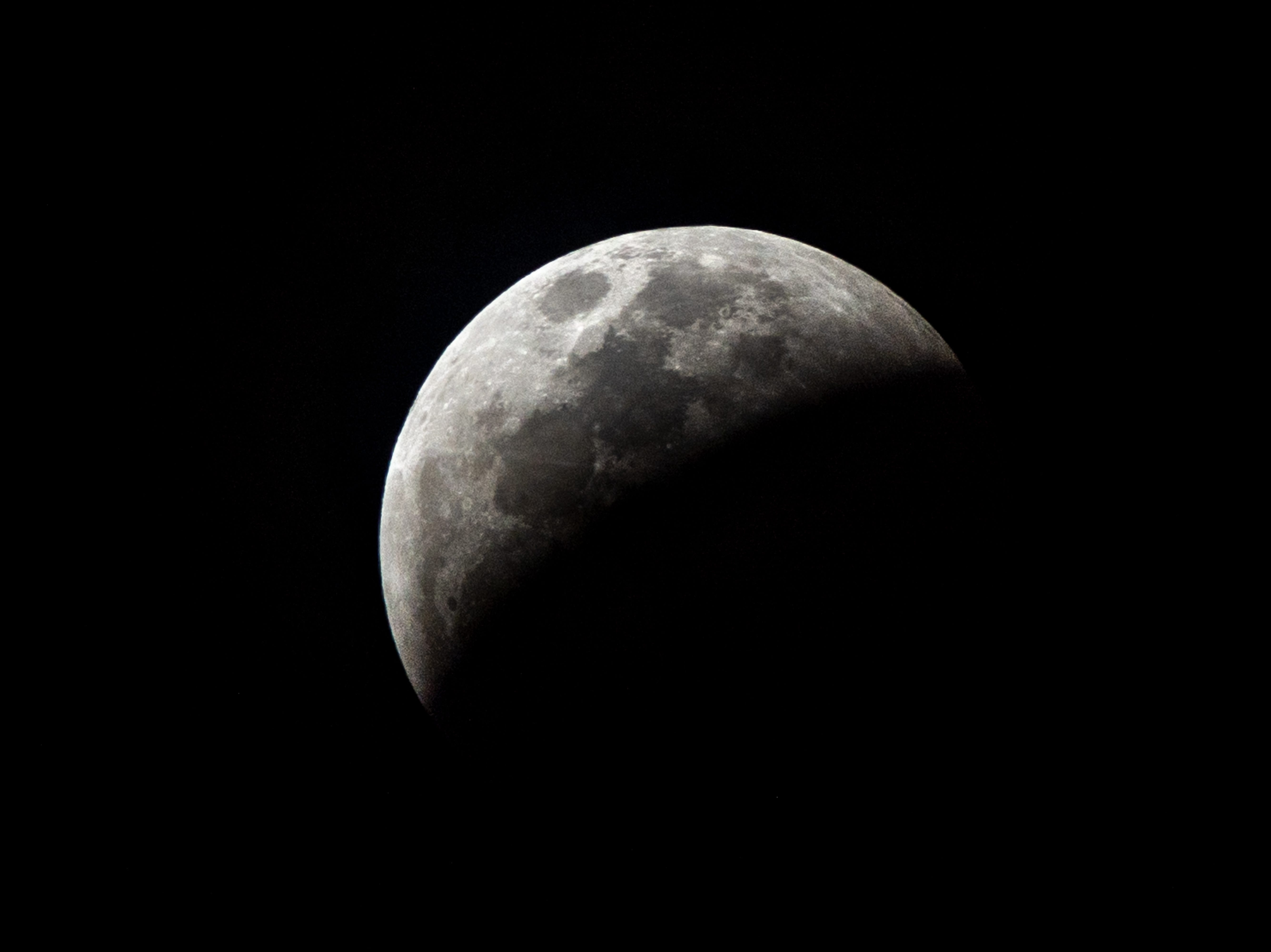 The so-called Super Blood Wolf Moon total lunar eclipse reaches a partial phase where more than half of the Moon is immersed in Earth's umbra, on Sunday January 20, 2019, in Miami, Florida. - The January 21 total lunar eclipse will be the last one until May 2021, and the last one visible from the United States until 2022. (Photo by Gaston De Cardenas / AFP)