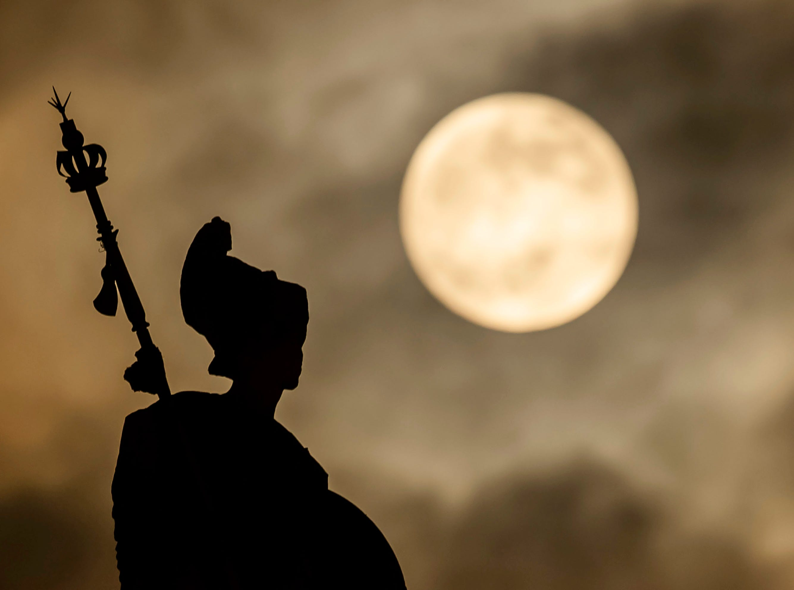 A supermoon rises above the Britannia statue at Hull Guildhall ahead of the Lunar Eclipse, in Hull, England, Sunday, Jan. 20, 2019.