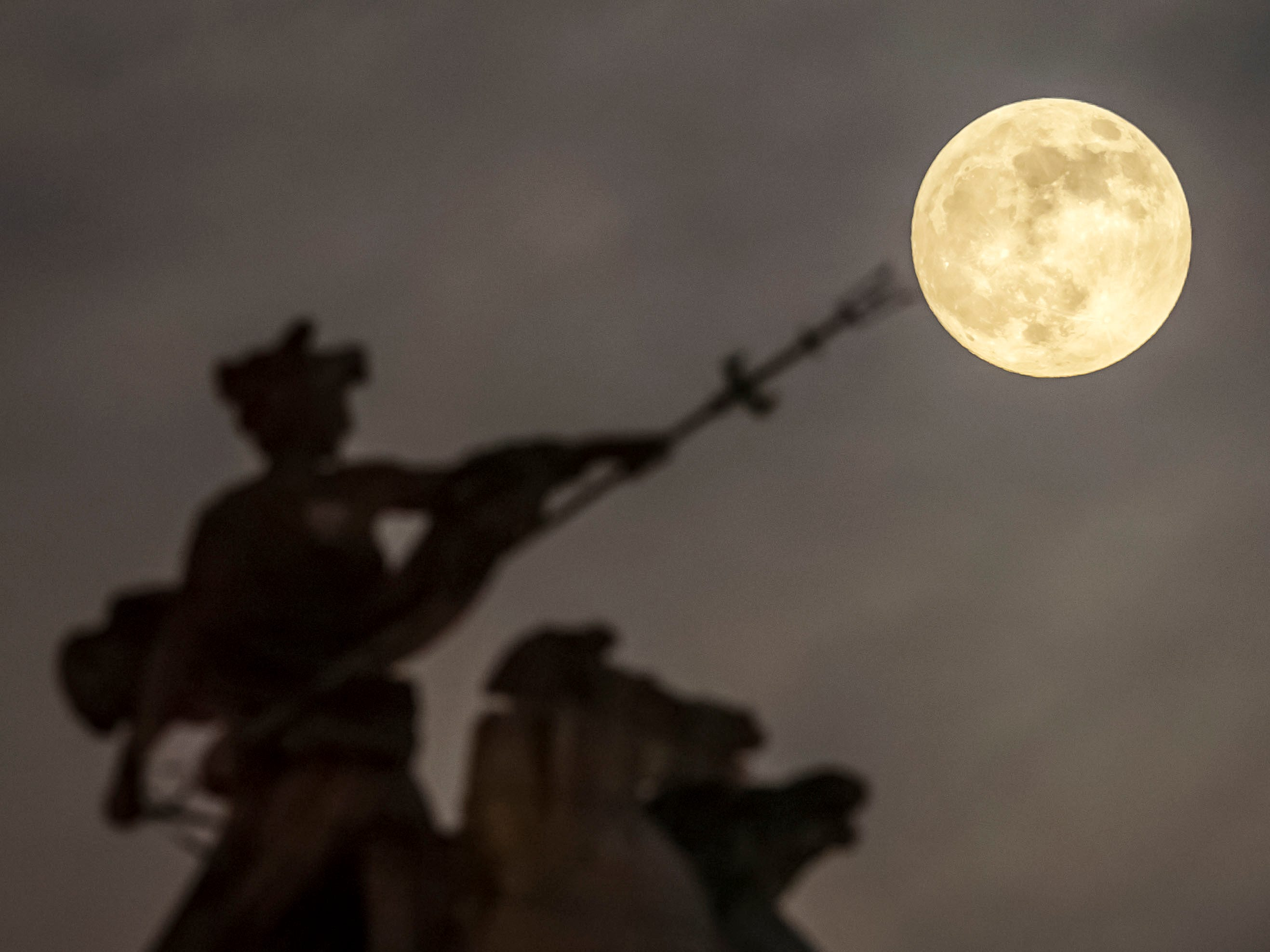 A super moon rises above the 'Maritime Prowess' by Albert Hemstock Hodge on the Guild Hall ahead of the Lunar Eclipse, in Hull, England, Sunday, Jan. 20, 2019.