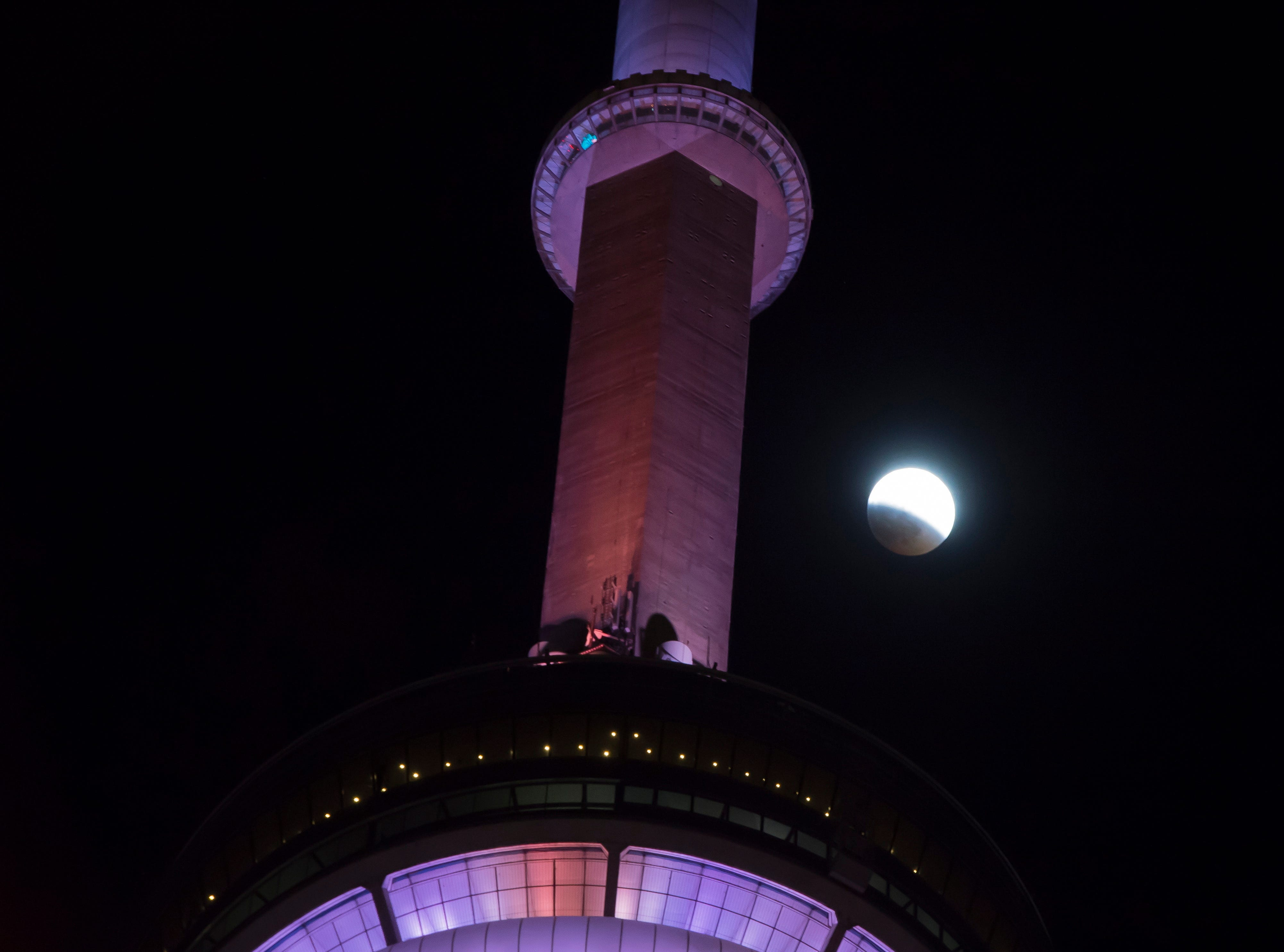 An eclipse of the moon progresses behind the CN Tower in Toronto on Sunday, Jan. 20, 2019. The entire eclipse will exceed three hours. Totality - when the moon's completely bathed in Earth's shadow - will last an hour. Expect the eclipsed, or blood moon, to turn red from sunlight scattering off Earth's atmosphere.