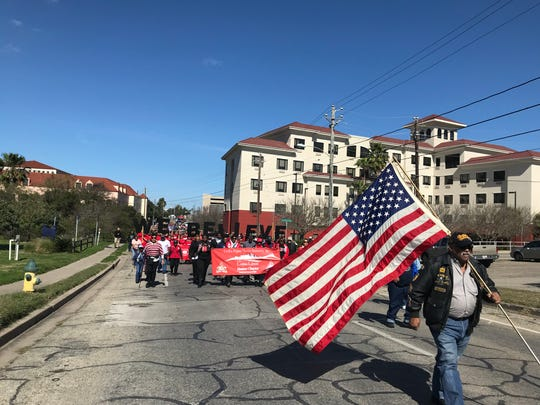 A Corpus Christi war veteran holds an American flag as he leads the 33rd annual Martin Luther King Holiday Celebration MLK Commemorative March on Jan. 21, 2019.