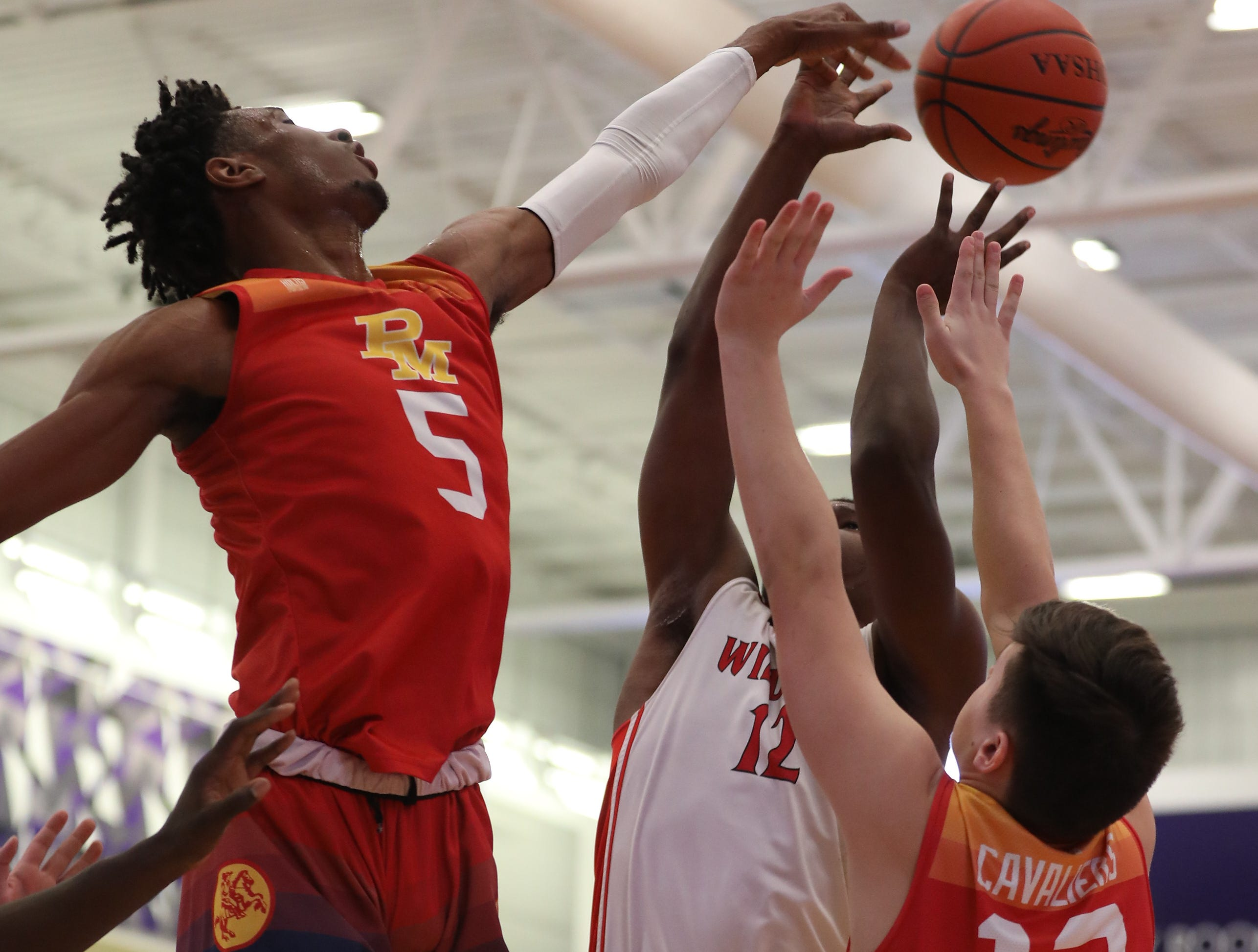 Purcell Marian forward A.J. Garrett (5) blocks a shot by Deer Park's DeShaun McEntire during their basketball game at the Midwest King Classic at Wade E Miller Gymnasium Sunday, Jan. 20, 2019.