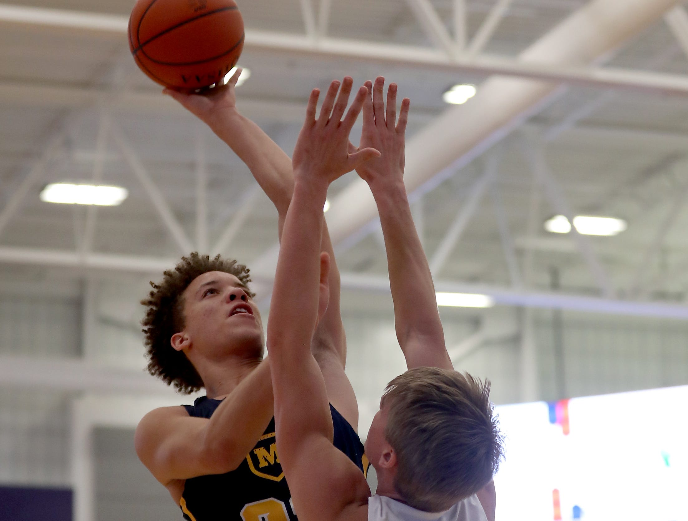 Moeller guard Max Land (22) shoots over Lakota East forward Grant Spicer during their game in the Midwest King Classic, Sunday, Jan. 20, 2019.