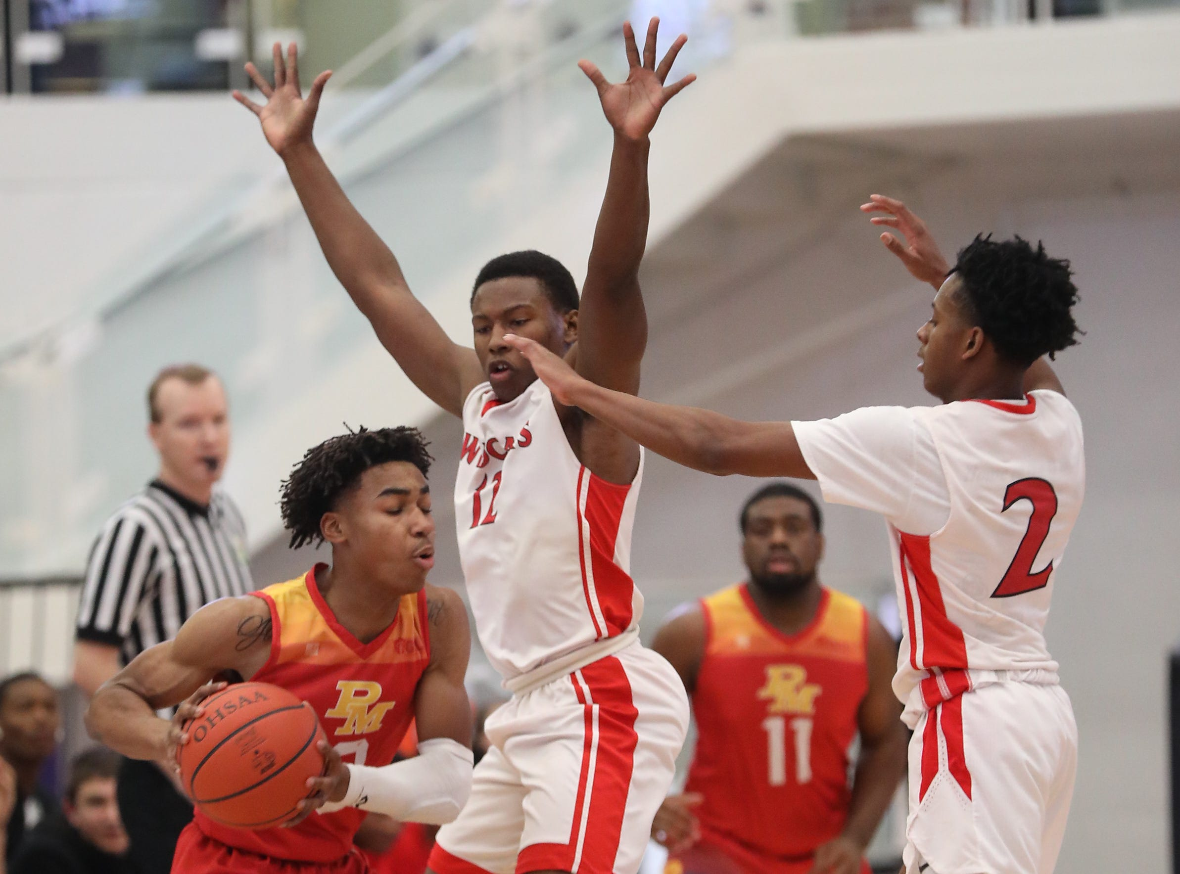 Purcell Marian guard Clark Jefferson (3) is surrounded by Deer Park defenders  Steve Gentry and DeShaun McEntire during their basketball game at the Midwest King Classic Sunday, Jan. 20, 2019.