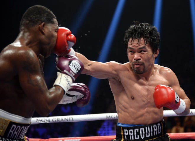 Manny Pacquiao (black trunks) and Adrien Broner (purple/gold trunks) box during a WBA welterweight world title boxing match at MGM Grand Garden Arena. Pacquiao won via unanimous decision.