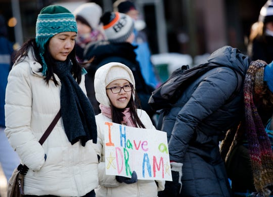 "Naomi Brown, 10, holds a sign that reads ""I have a dream"" while marching with her mother, Ai Li Brown, during the 44th annual Martin Luther King Jr. Day Memorial March on Monday, Jan. 21, 2019 from the Freedom Center to Music Hall in Cincinnati."