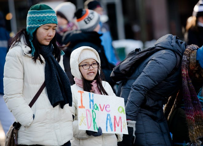 """Naomi Brown, 10, holds a sign that reads """"I have a dream"""" while marching with her mother, Ai Li Brown, during the 44th annual Martin Luther King Jr. Day Memorial March on Monday, Jan. 21, 2019 from the Freedom Center to Music Hall in Cincinnati."""