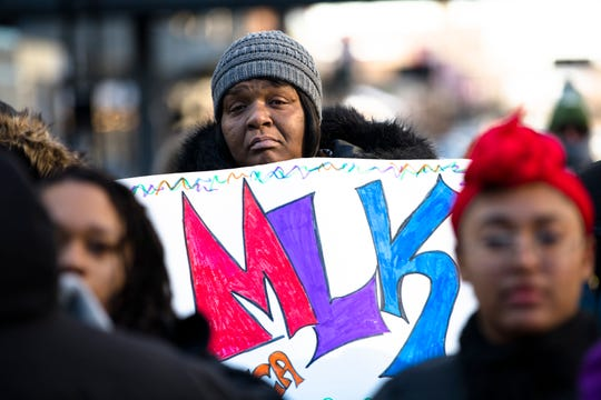 Keya Curtis holds a sign while marching in the 44th annual Martin Luther King Jr. Day Memorial March on Monday, Jan. 21, 2019 from the Freedom Center to Music Hall in Cincinnati.