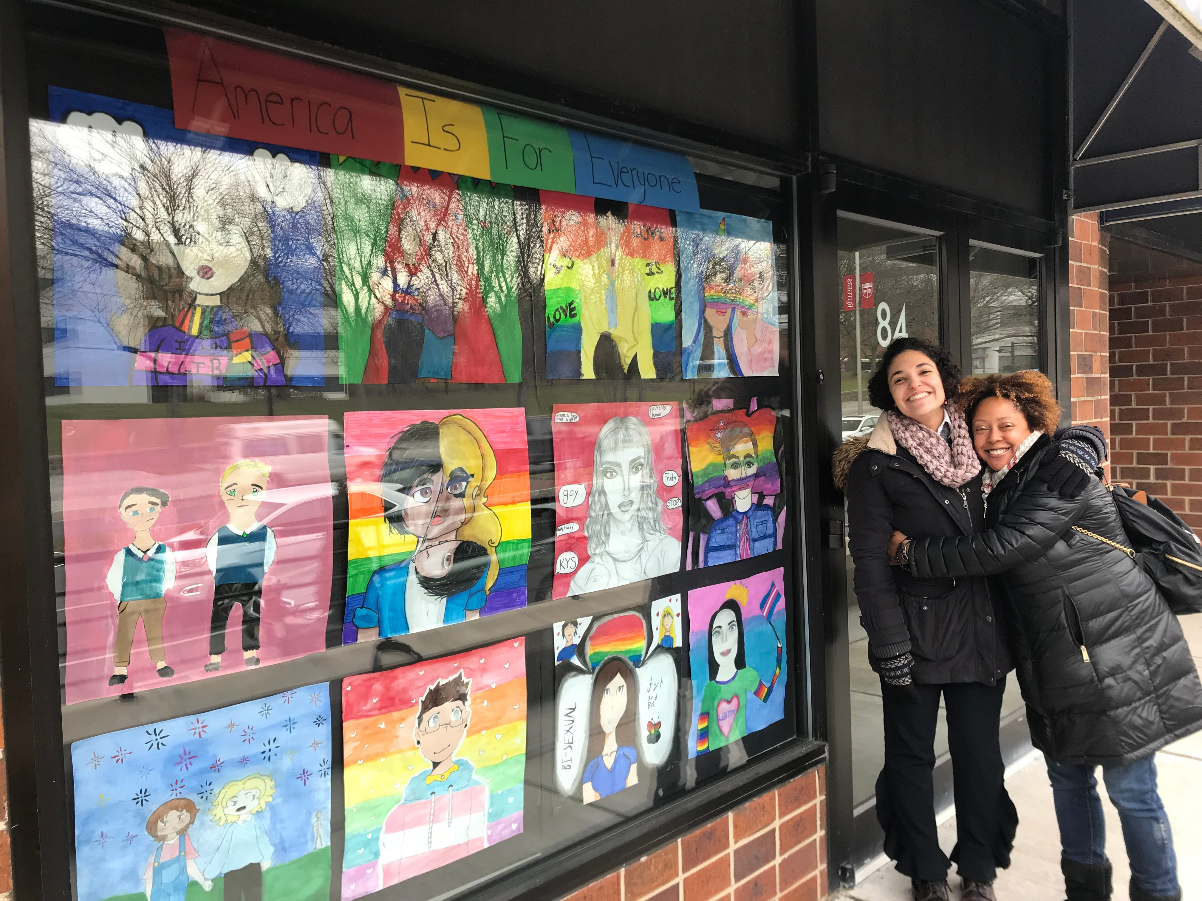 "New Brunswick Cultural Center's Sarah Ferreira and Tracey O'Reggio Clarke, two of the organizers of Windows of Understanding, are pictured with New Brunswick Middle School Art Club's ""America is for Everyone"" at Voices of 9/11 on Albany Street in New Brunswick."