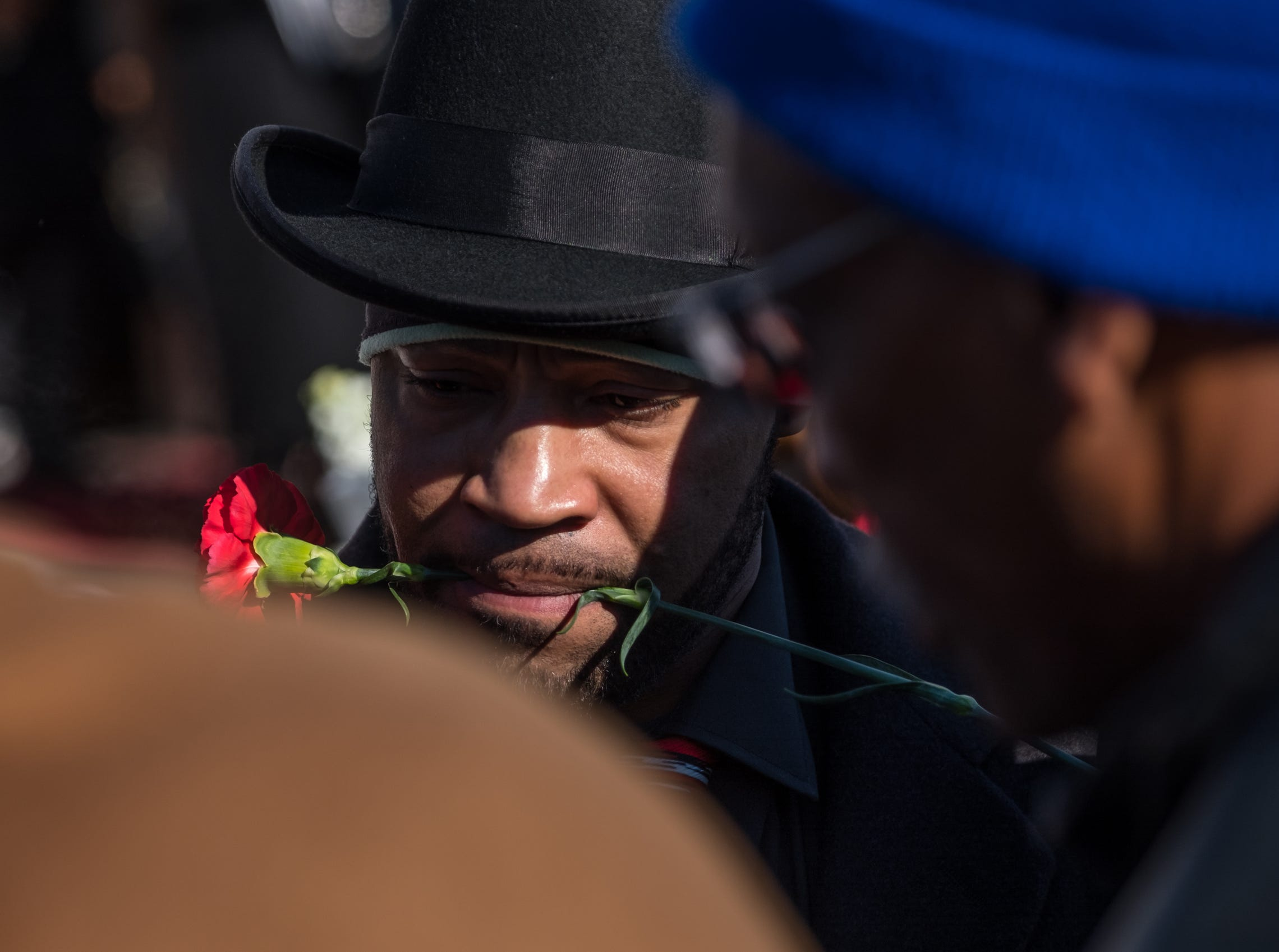 Mark Barker carries a rose from the casket of his brother Rudy Barker while loading it into the hearse during his brother's funeral at Hutchison Funeral Home in Detroit on Monday, January 21, 2019. Barker was known for his impressions of late civil rights leader Martin Luther King Jr. and was buried on the national holiday honoring his hero.