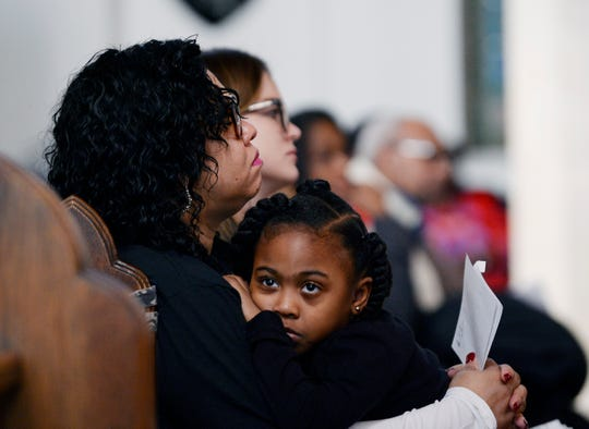 Five-year-old A'mya Winston sits in her mother Nia Winston's arms. Nia Winston is President of Unite Here Local 24.