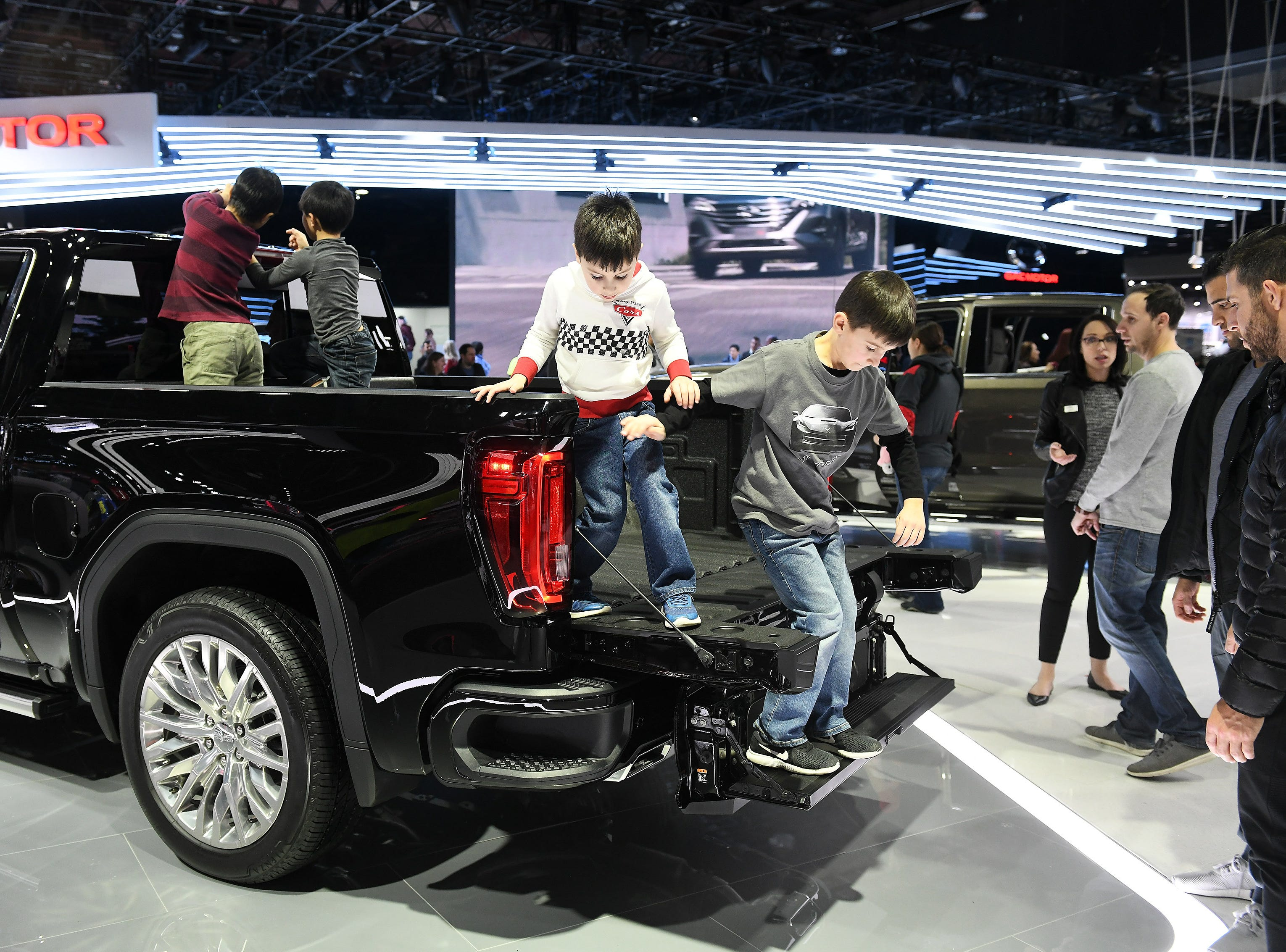 Cristiano Vittorini, 5, left, and his brother, Valentino Vittorini, 6, of Rochester Hills climb out of the bed of a GMC Denali using the GMC multi-pro tail gate.