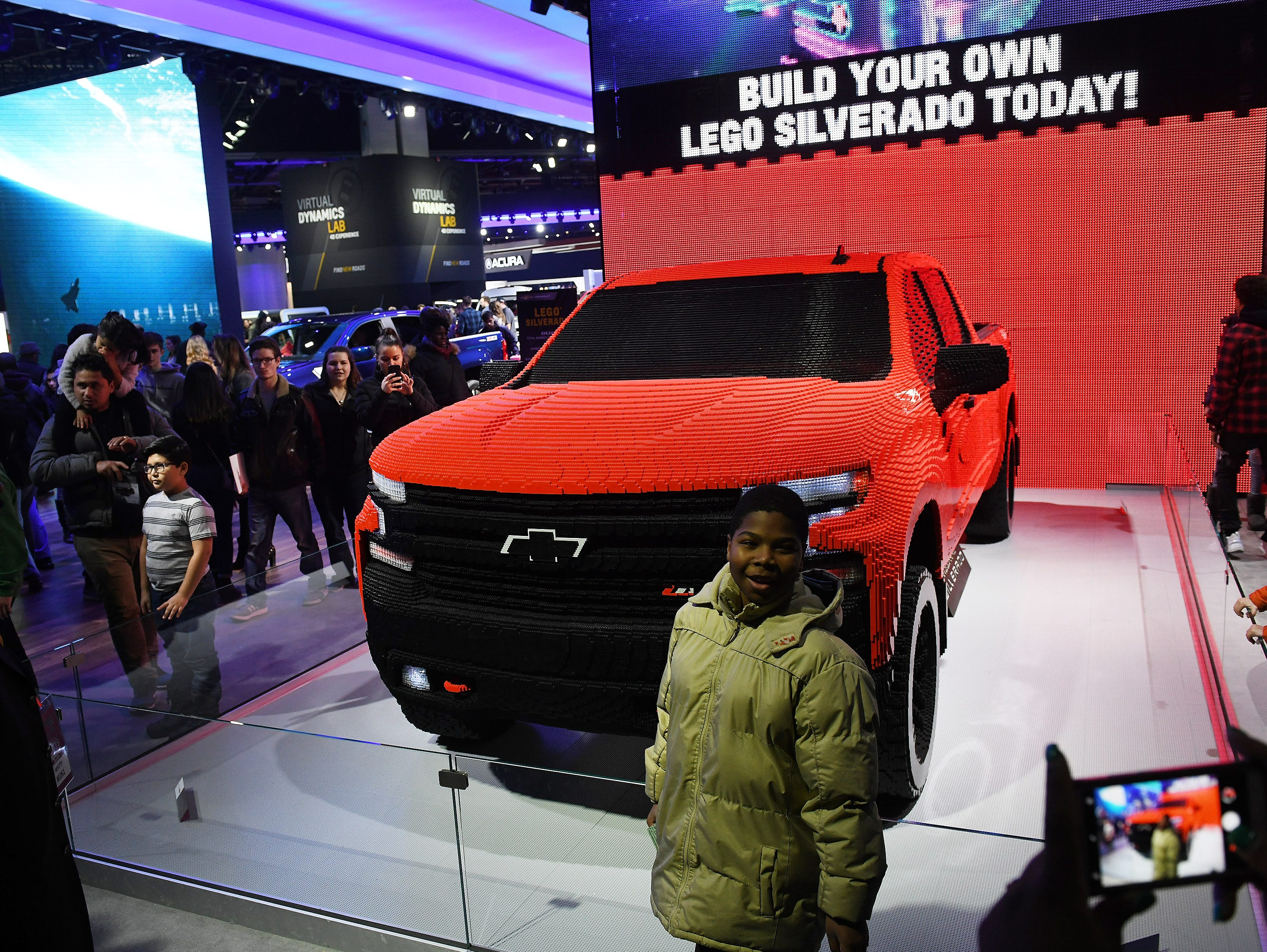 Malachi Allen, 11, of Detroit poses while his mother, Noel Allen takes a photo of him in front of the Lego version of a Chevy Silverado at the North American International Auto Show at Cobo Center in Detroit on January 20, 2019.