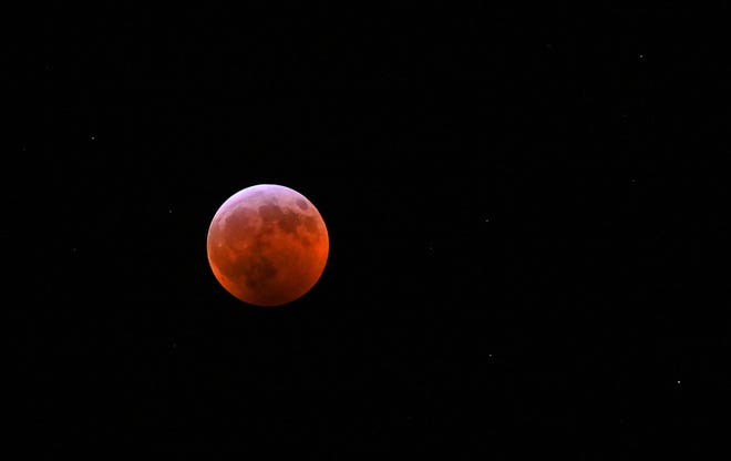 The blood-red moon is viewed from Mid-Michigan with stars faintly visible in the background.