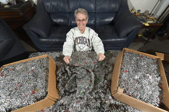Allan Levy of Canton is surrounded by a portion of the 550,467 pull tabs collected over six years.