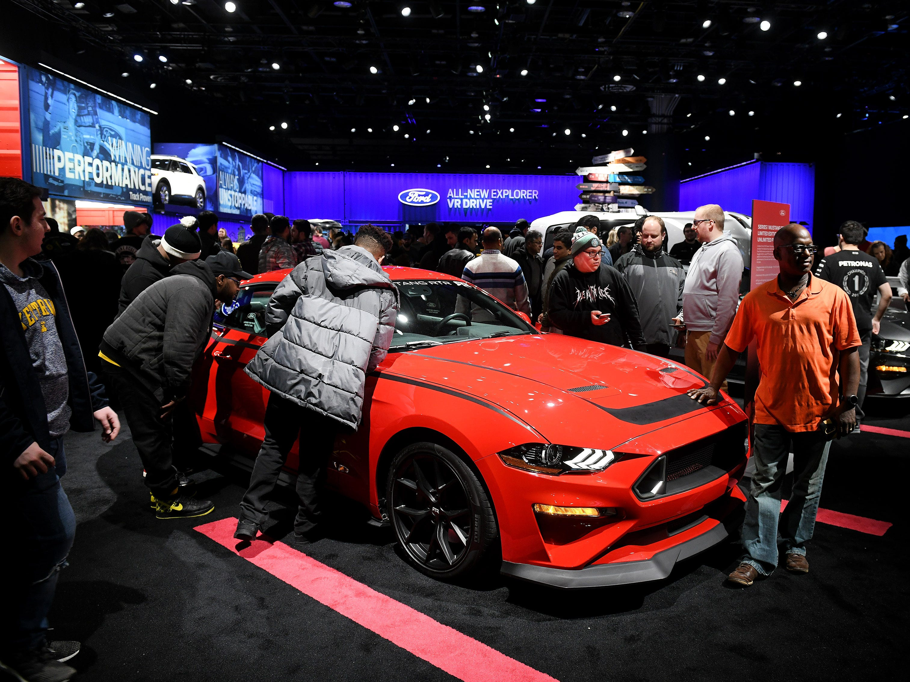Oscar Murdock, right, of Flint poses with a Mustang RTR while his wife, Jessie, out of the frame, takes a photo.
