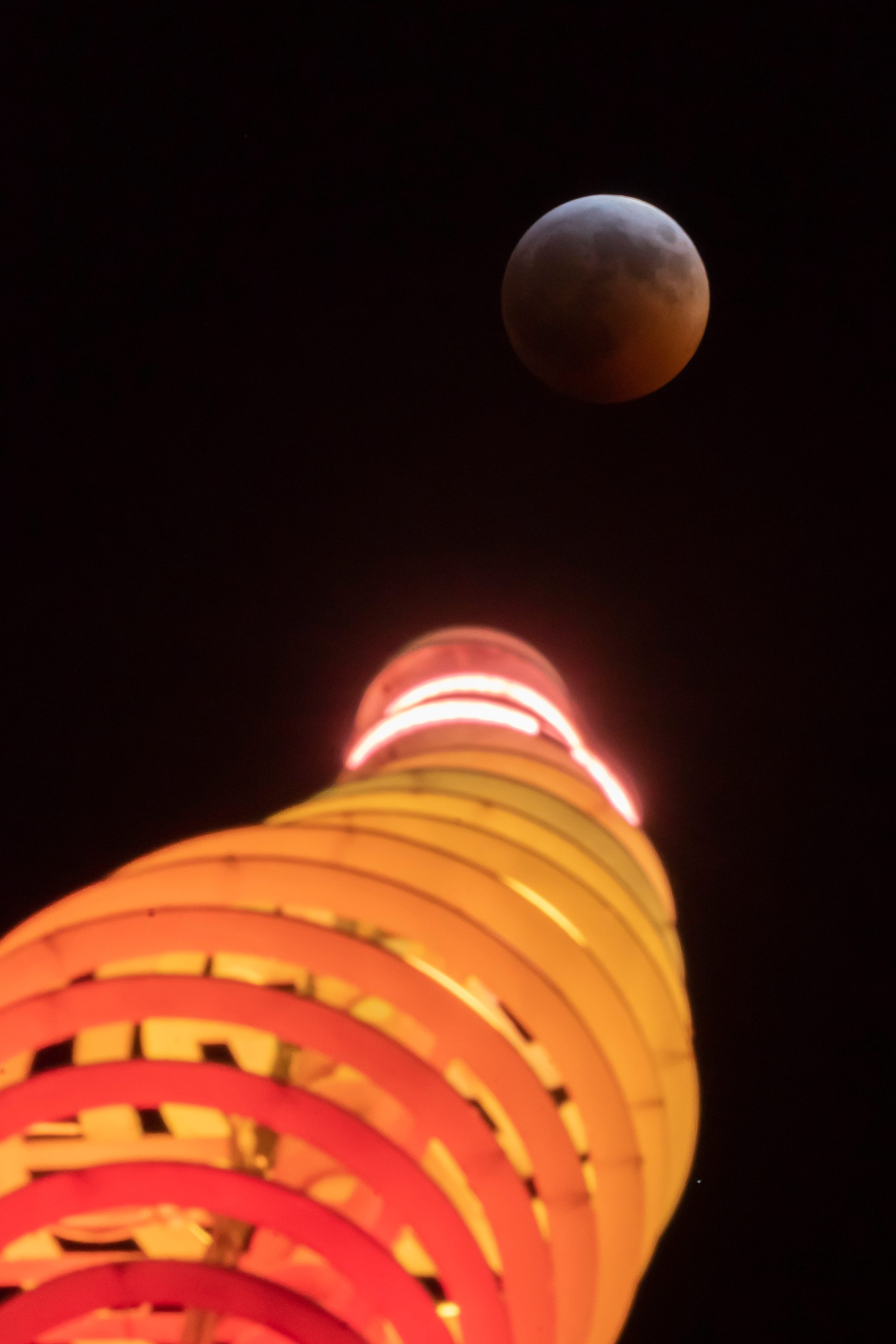A super blood wolf moon rises over a light sculpture in downtown Detroit, January 20, 2019.   (David Guralnick / The Detroit News)