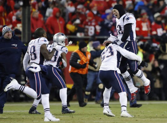 New England Patriots quarterback Tom Brady (12) celebrates with his teammates after the AFC Championship NFL football game Sunday. The Patriots defeated the Chiefs 37-31 in overtime.