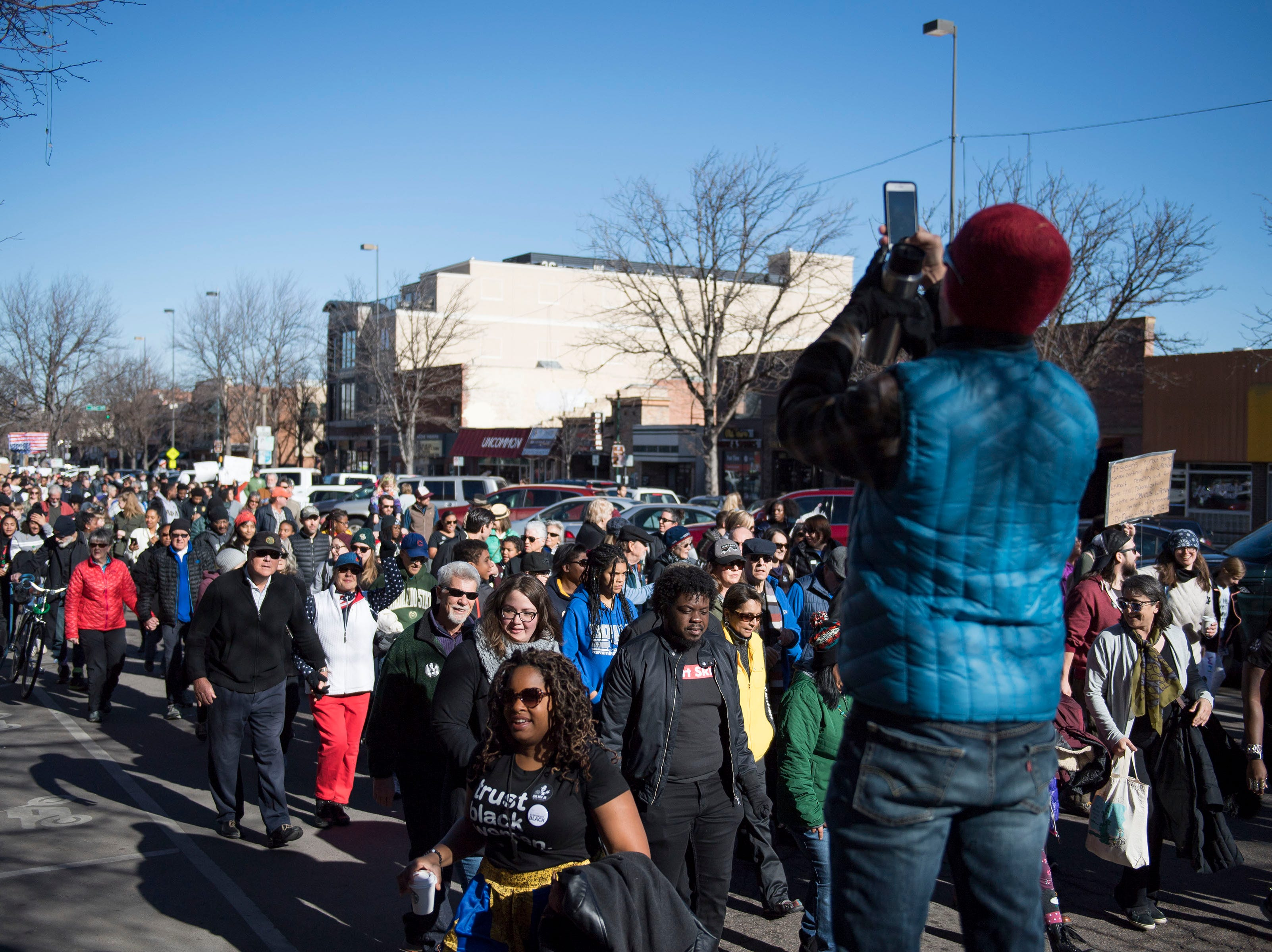 Seth Lorson takes a photo of the march heading down South College Avenue during the Dr. Martin Luther King, Jr. March & Celebration on Monday, Jan. 21, 2019, in Fort Collins, Colo.