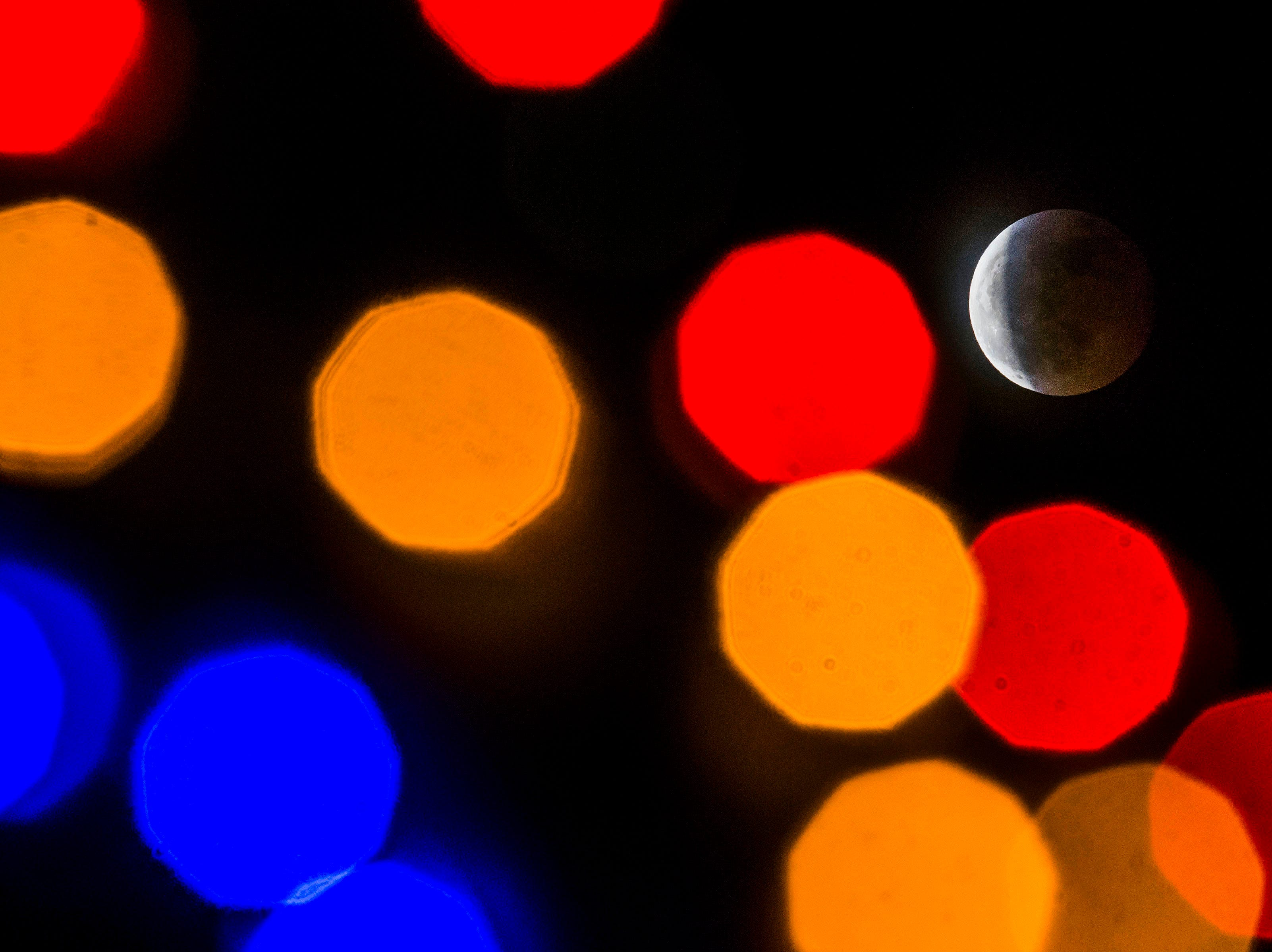 A super blood wolf moon total lunar eclipse shines behind holiday lights in front of the main entrance of Genesis Health Clubs on Sunday, Jan. 20, 2019, in Fort Collins, Colo.