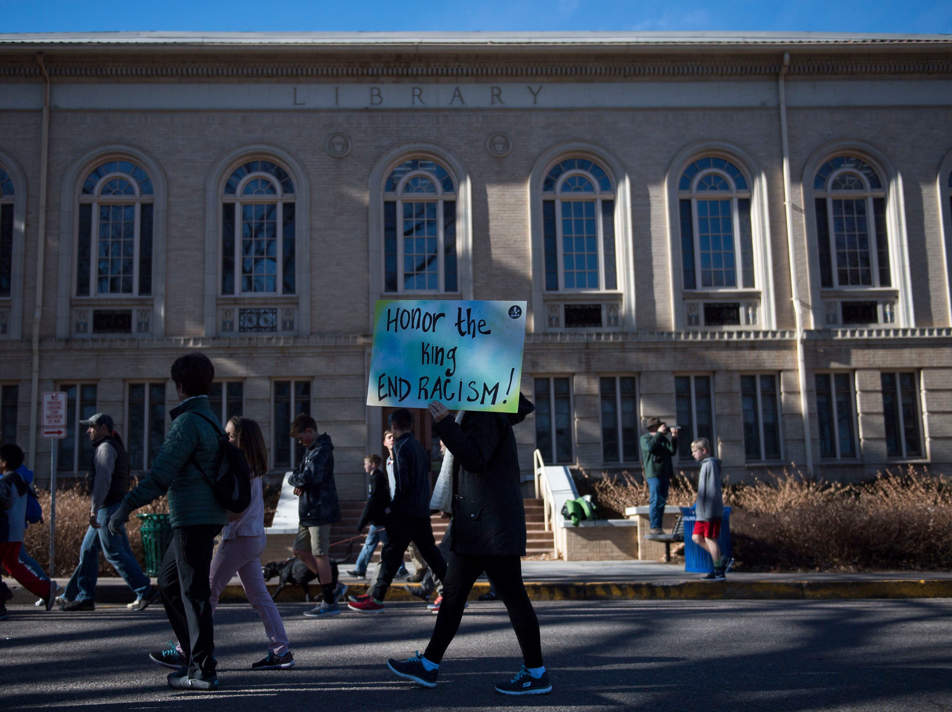 First year social work student Shannon Modec holds a sign while marching with the crowd around The Oval during the Dr. Martin Luther King, Jr. March & Celebration on Monday, Jan. 21, 2019, on the Colorado State University campus in Fort Collins, Colo.
