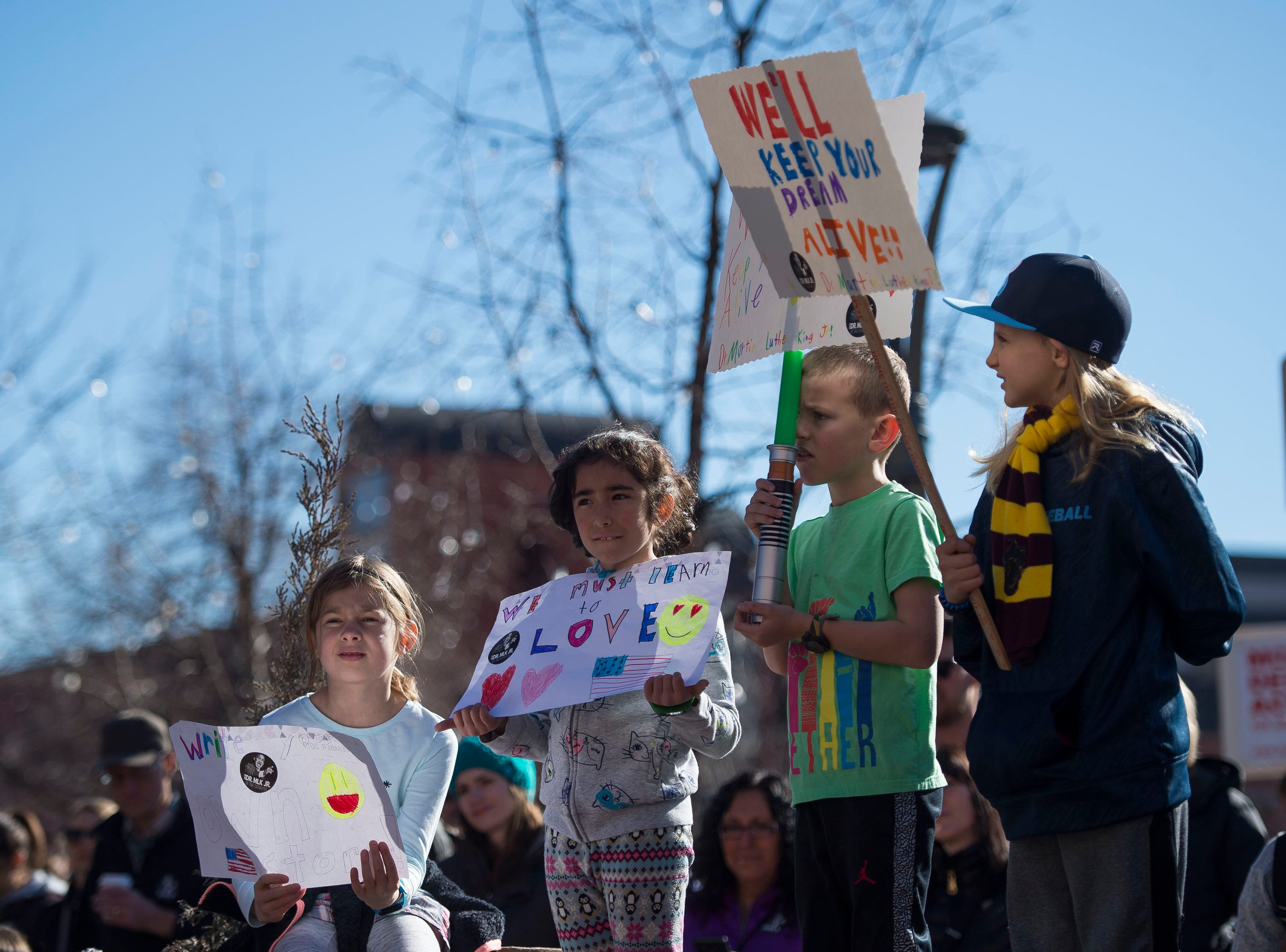 Young march participants from Shepardson Elementary School, from left, Nina Demmler, 9, Riley Ward, 8, Caden Wallace, 8, and Audrey Abernathy, 8, hold up their signs in Old Town Square at the Dr. Martin Luther King, Jr. March & Celebration on Monday, Jan. 21, 2019, in Fort Collins, Colo.