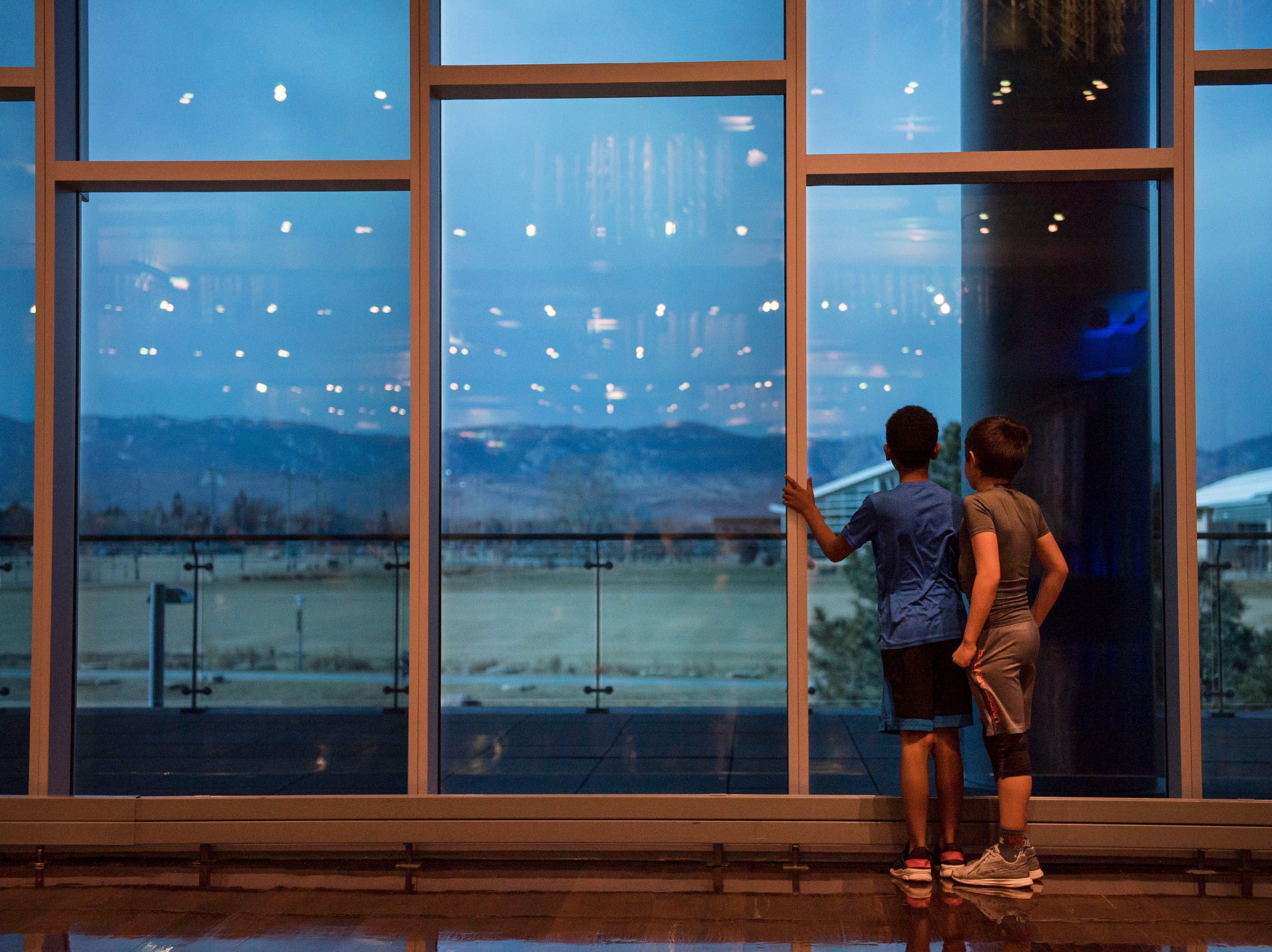 Zeke Shrull, 10, and Tristan Gonzales, 9, look out the West-facing windows while waiting for the Dr. Martin Luther King, Jr. March & Celebration to continue on Monday, Jan. 21, 2019, at the Lory Student Center on the Colorado State University campus in Fort Collins, Colo.