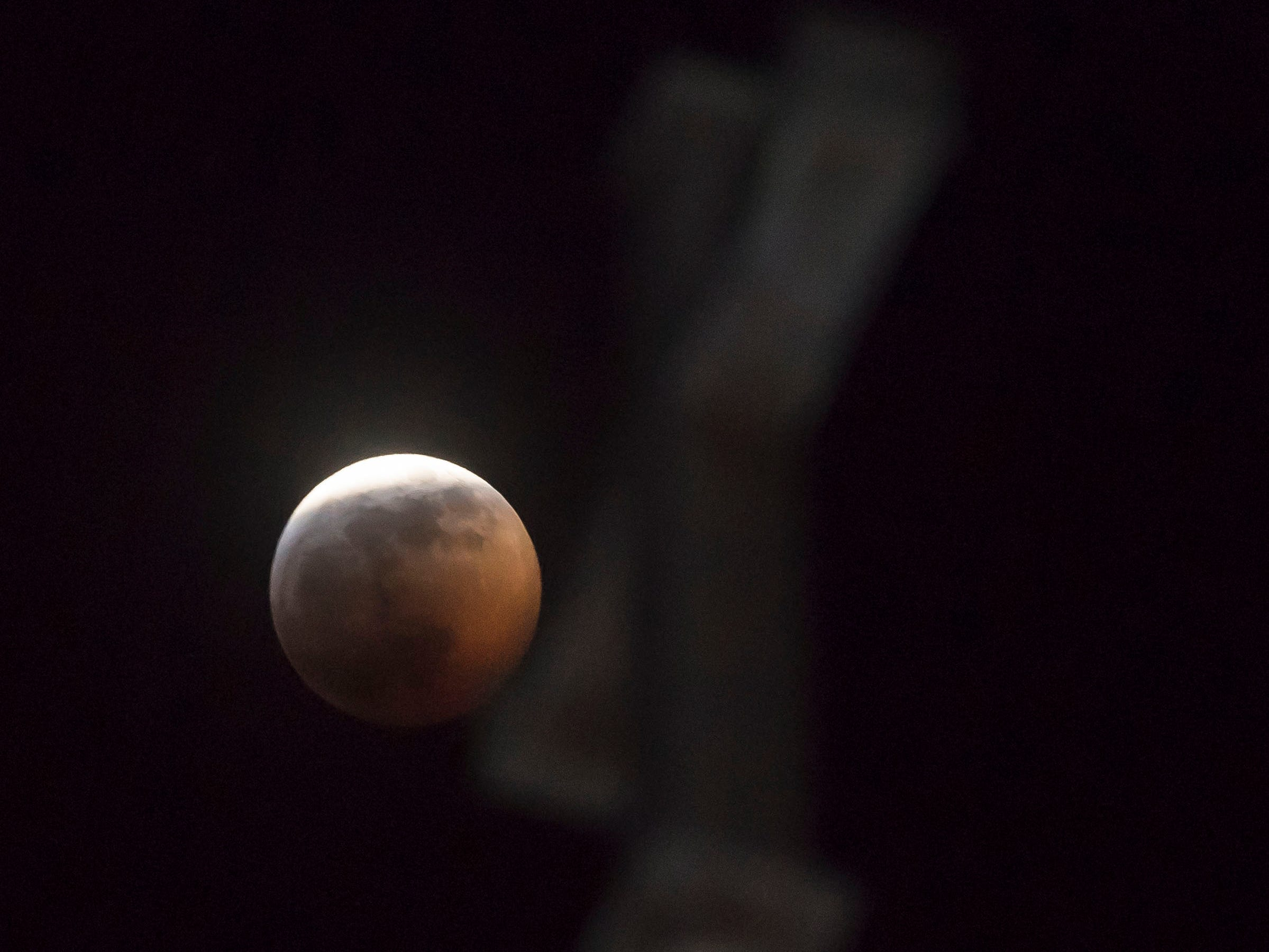 A super blood wolf moon total lunar eclipse shines behind a cross on St Joseph's Catholic Church on Sunday, Jan. 20, 2019, in Fort Collins, Colo.