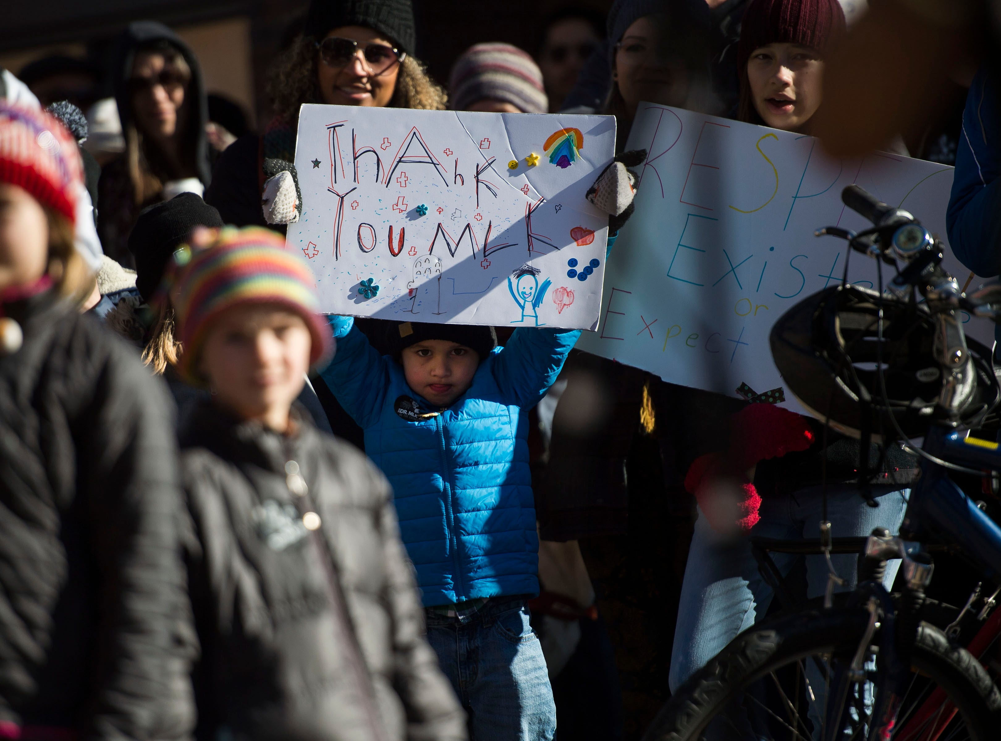 A young march participant holds up his sign in Old Town Square during the Dr. Martin Luther King, Jr. March & Celebration on Monday, Jan. 21, 2019, in Fort Collins, Colo.