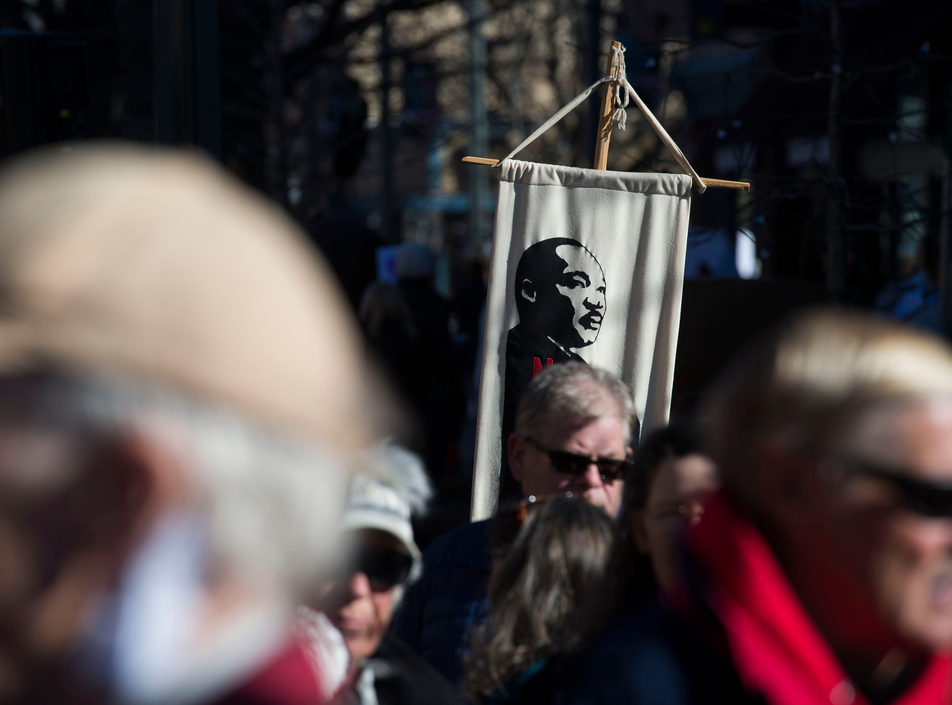 A march participant hold up a sign in Old Town Square before the Dr. Martin Luther King, Jr. March & Celebration on Monday, Jan. 21, 2019, in Fort Collins, Colo.