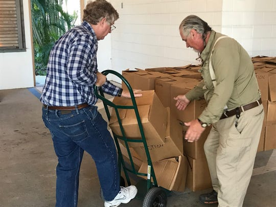 Rev. Ivan Corbin from Beach United Methodist Church and Mark Lafave, a former library board member, help put away books left over from the two-day book sale the library held this weekend. The second day of the sale was halted by the fatal stabbing of library director Leroy Hommerding.