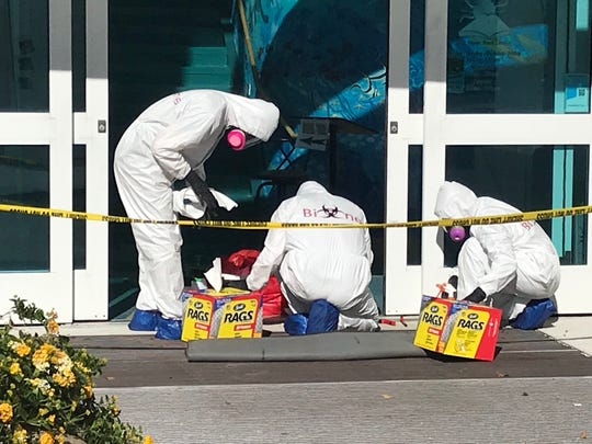 A hazardous materials crew from Bio-One of Fort Myers works cleans the front entrance at the Fort Myers Beach Public Library Monday. The entrance was where library director Leroy Hommerding was fatally stabbed Sunday.