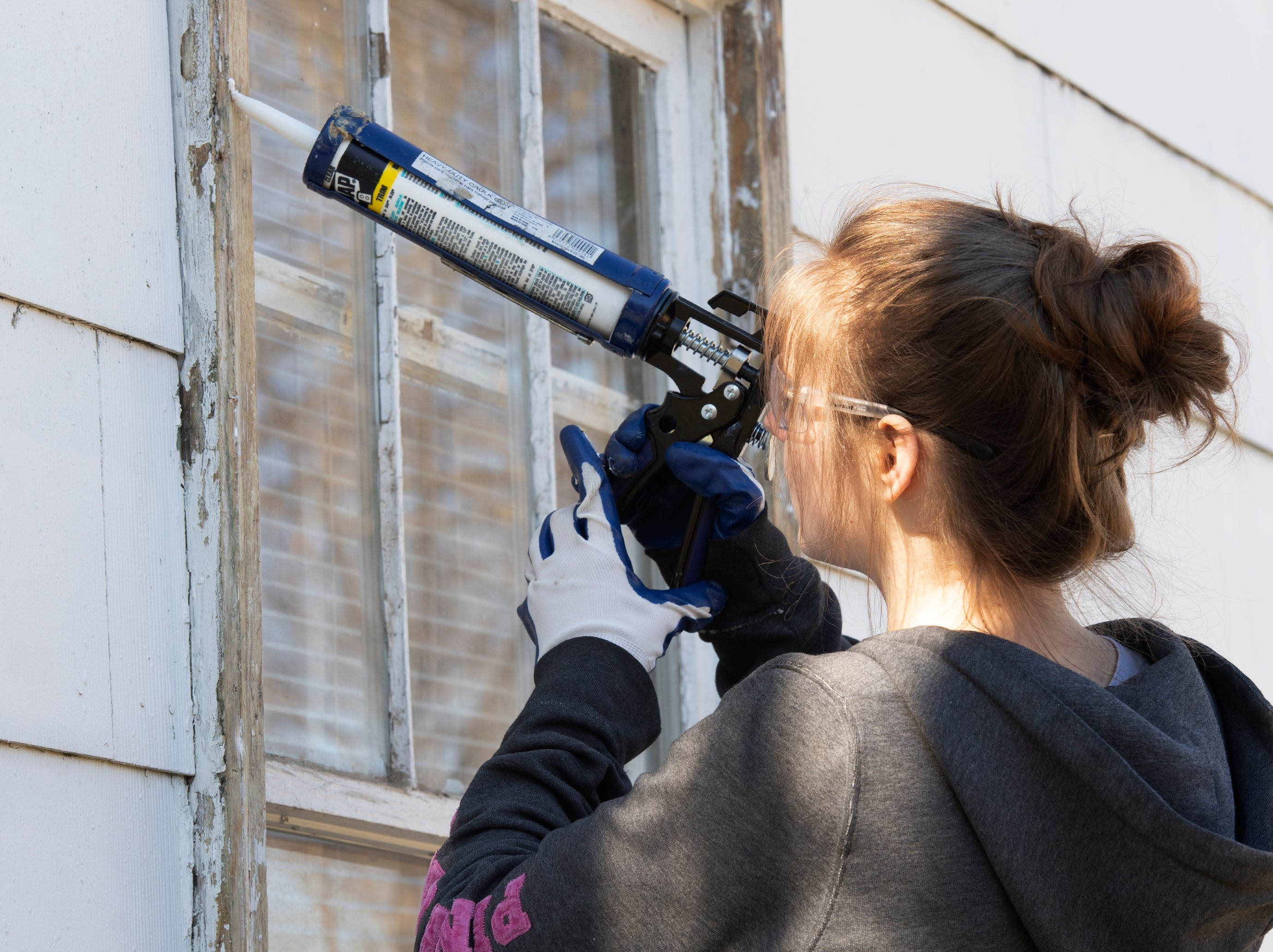 Bob Jones University sophomore Rebekah Stevens seals the windows on a home on Durham Street in Greenville on Martin Luther King, Jr. Day Monday, Jan. 21, 2019.