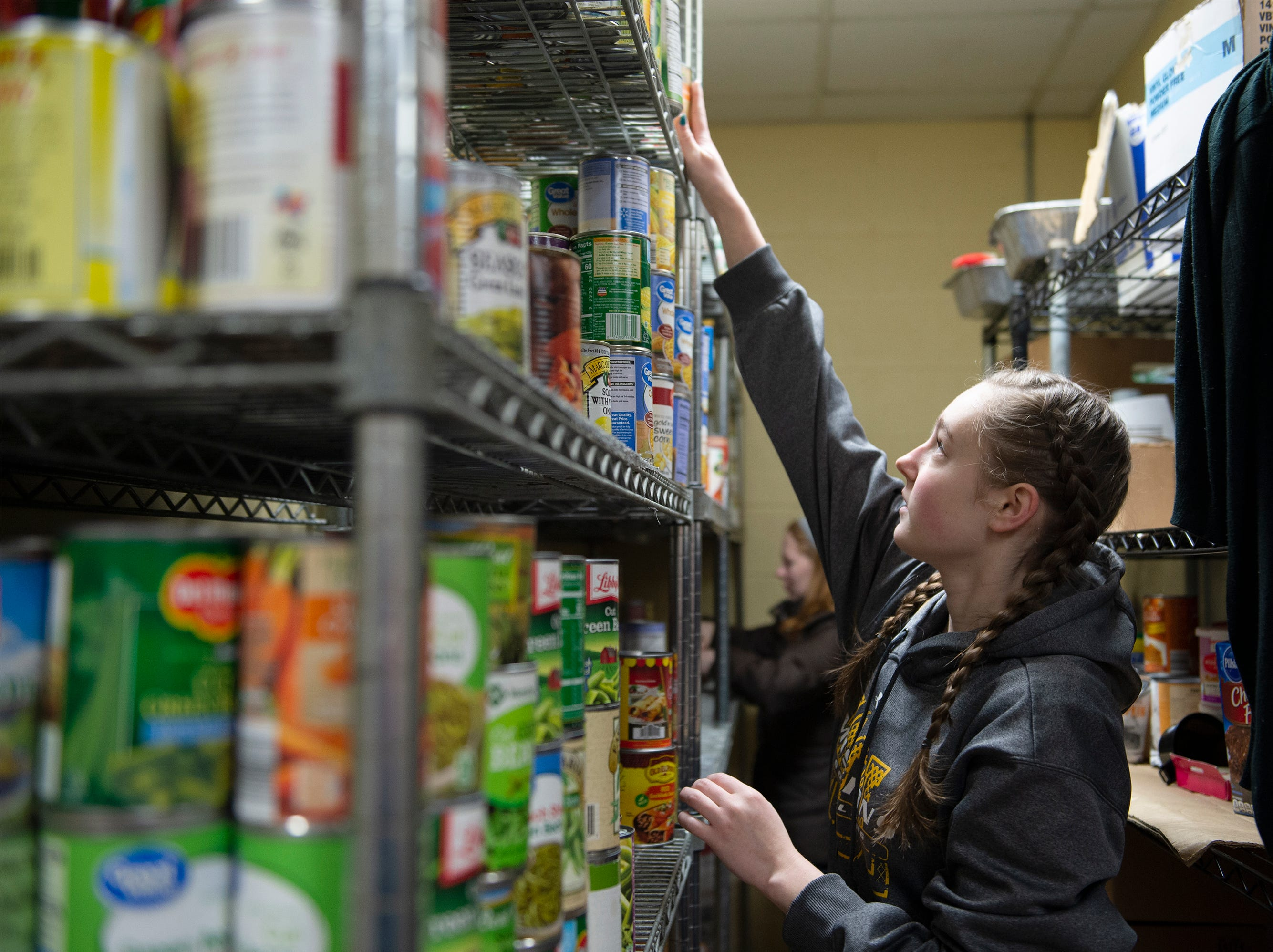 Bob Jones University sophomore Sarah Needham stacks donated foods on shelves in Miracle HillÕs Greenville Rescue Mission on Martin Luther King, Jr. Day Monday, Jan. 21, 2019.