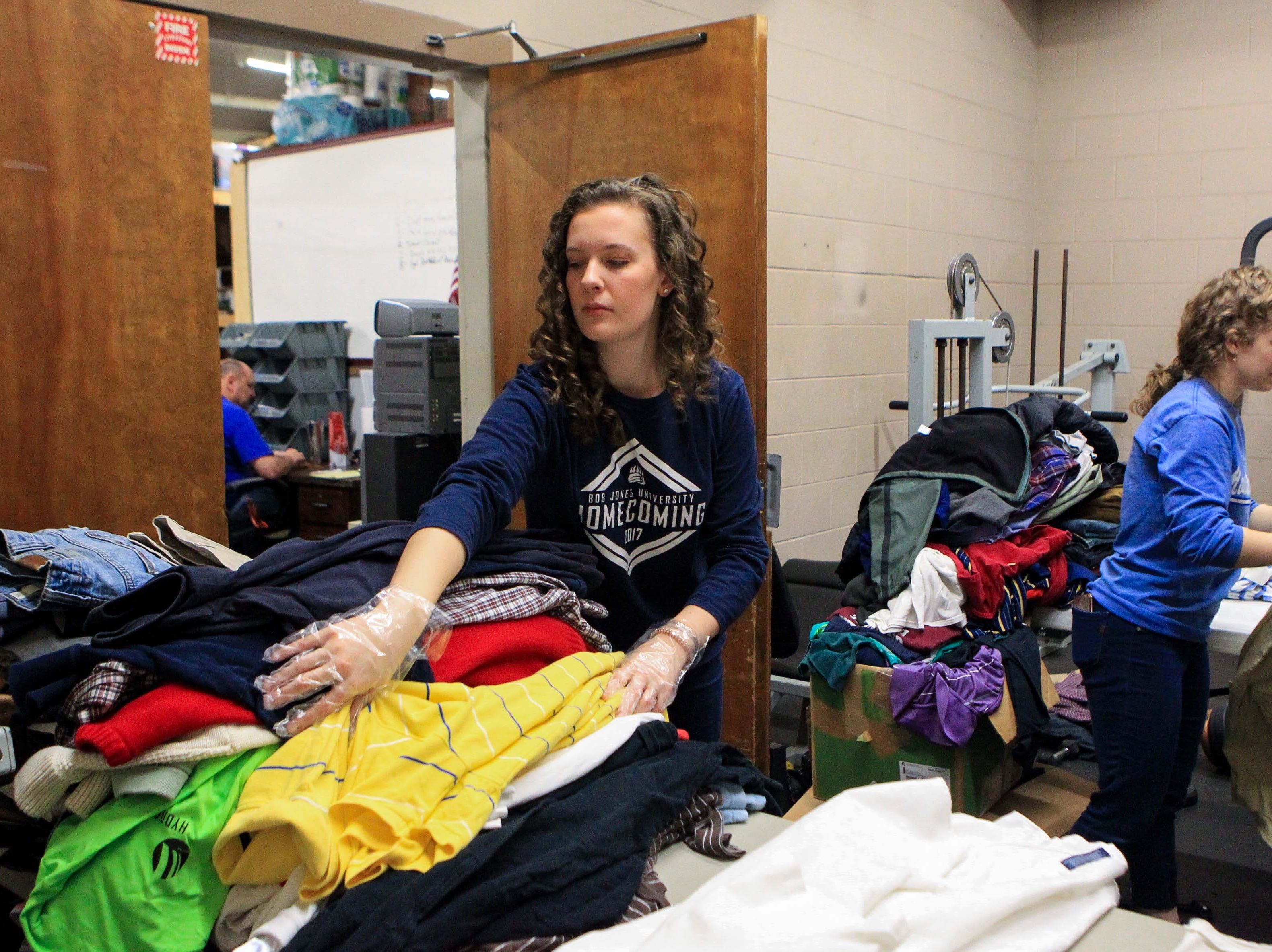 Jen Naas, a sophomore, keeps her pile tidy as Taylor Holland, a sophomore, sorts shirts at Miracle HillÕs Greenville Rescue Mission on Martin Luther King, Jr. Day Monday, Jan. 21, 2019.