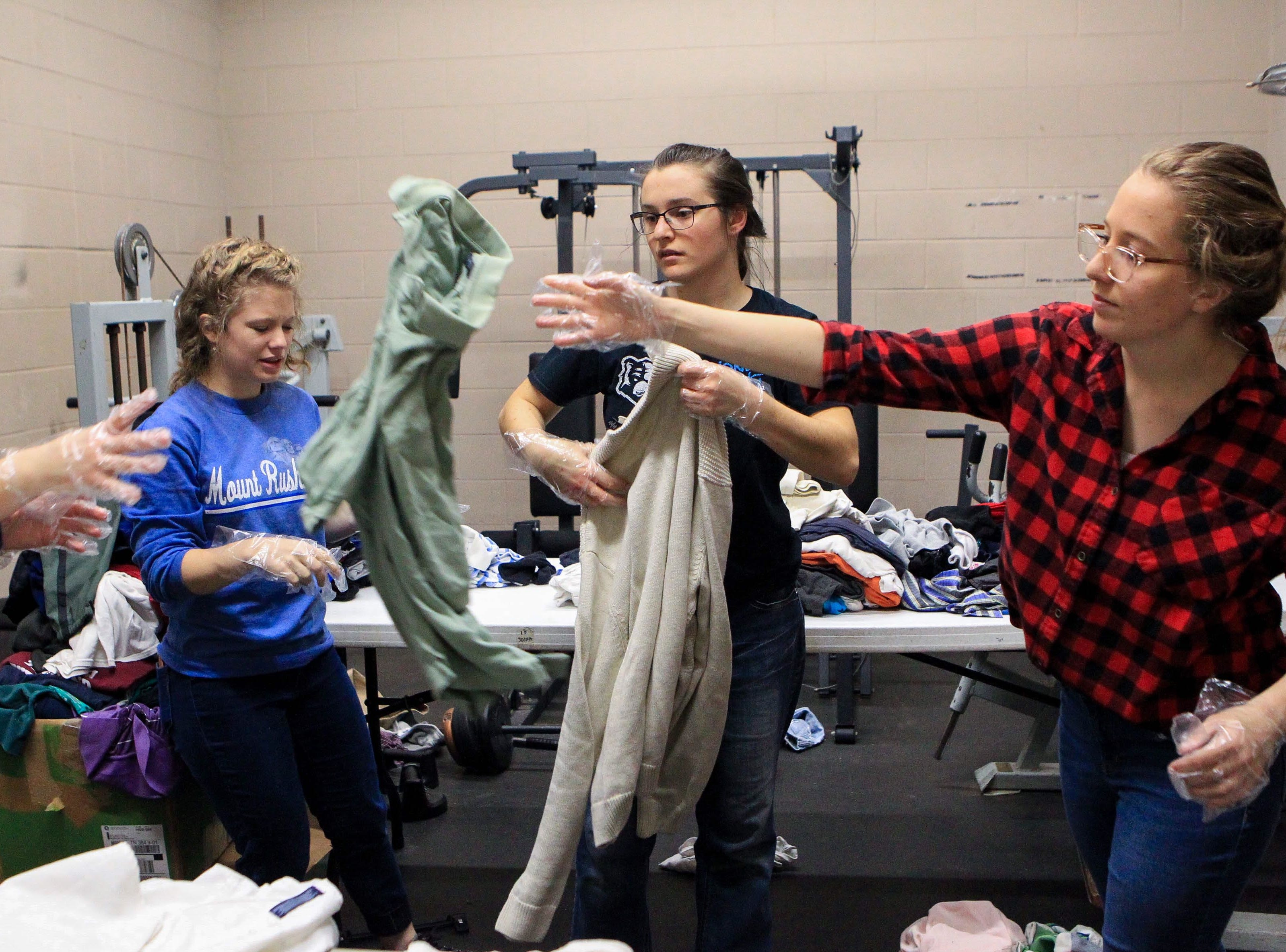 Sophomore Karen Mee tosses a shirt she just sorted as Suzanna Millington, a junior, and Taylor Holland, a sophomore, continue to sort at Miracle HillÕs Greenville Rescue Mission on Martin Luther King, Jr. Day Monday, Jan. 21, 2019.