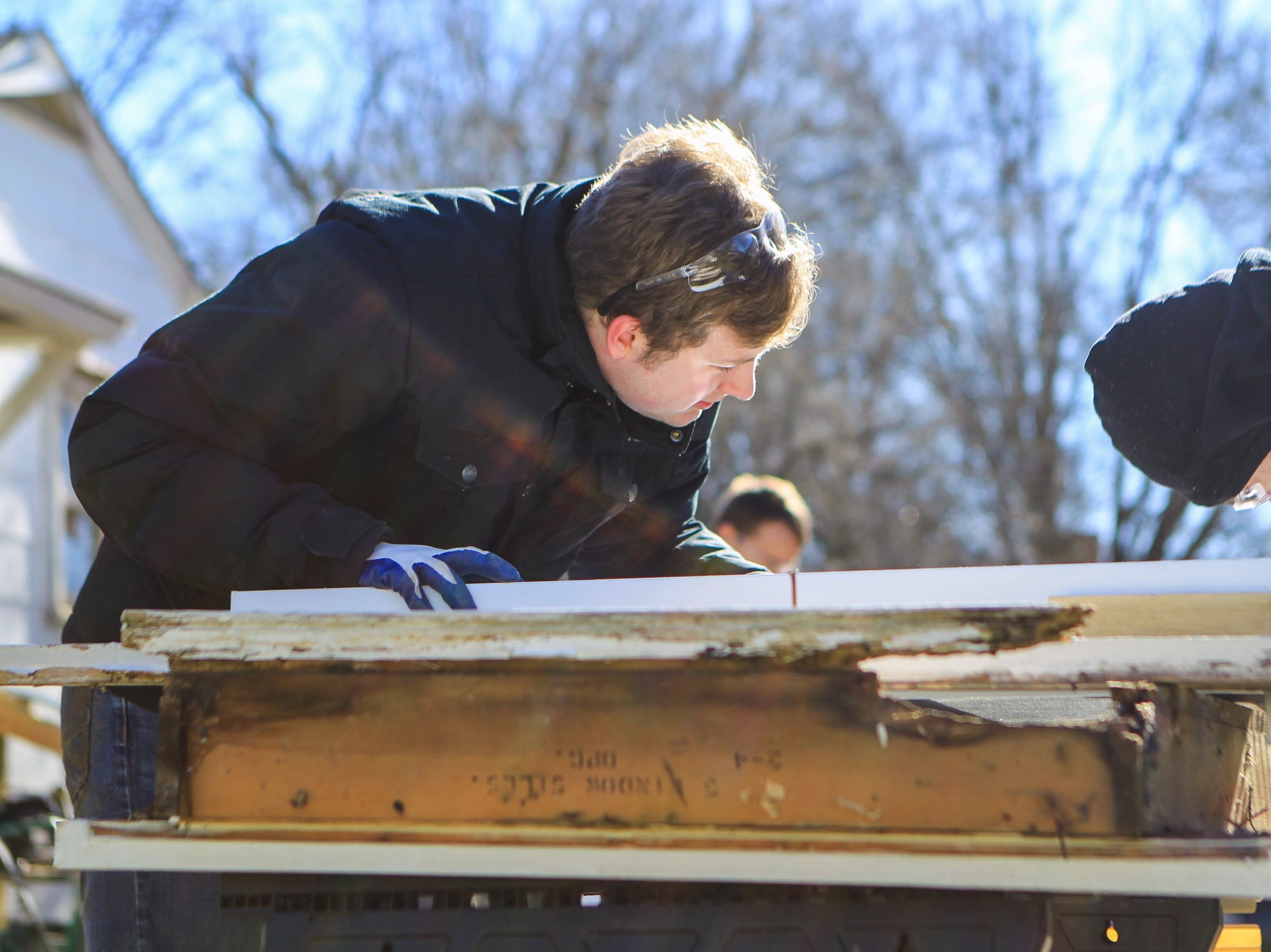 Bob Jones University's Micah Baughman, a sophomore, works on a home on Durham Street in Greenville on Martin Luther King, Jr. Day Monday, Jan. 21, 2019.