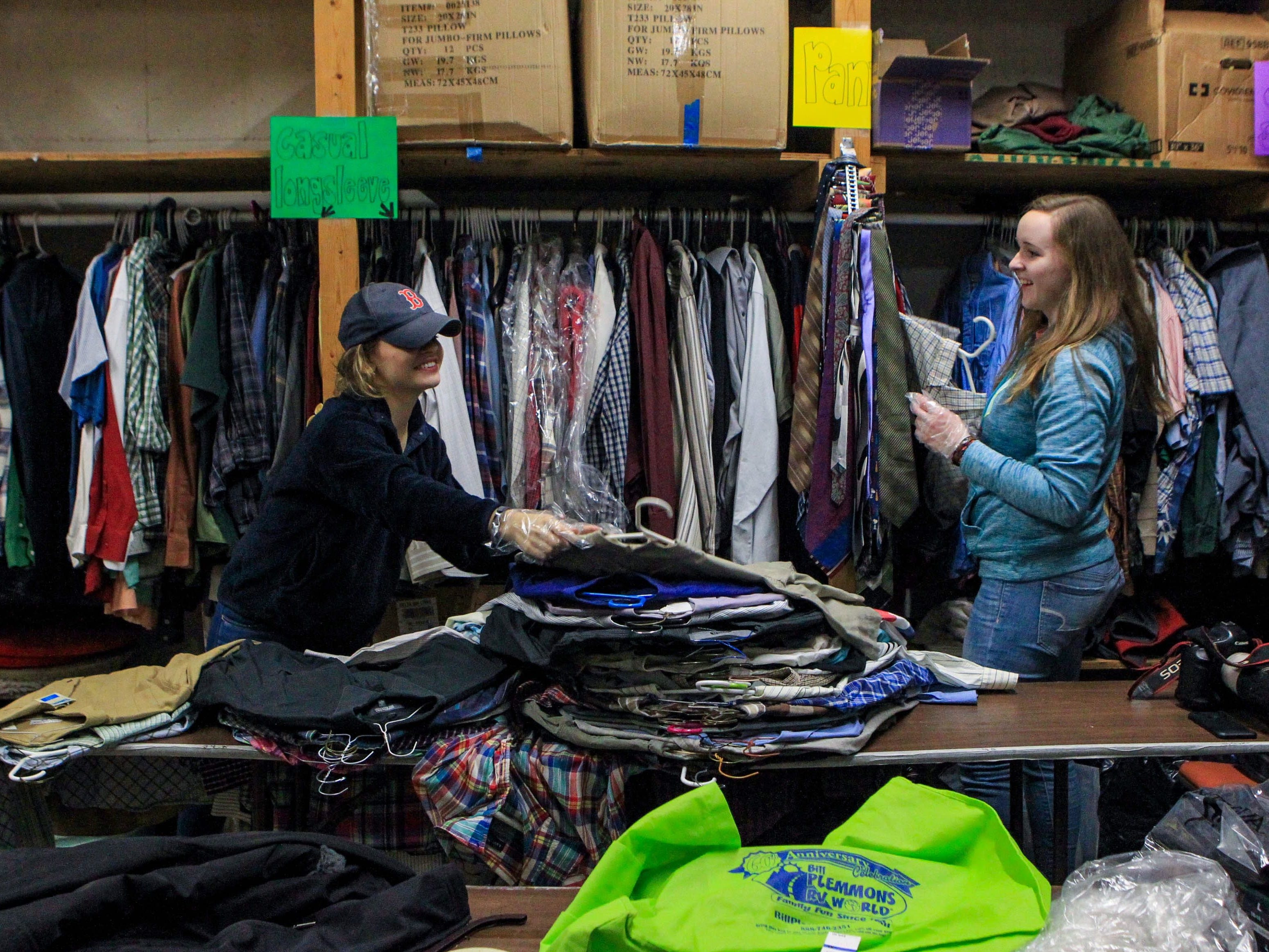 Sarah Rumpf, a sophomore, and Sarah Knutson, a sophomore, talk as they sort through shirt sizes at Miracle HillÕs Greenville Rescue Mission on Martin Luther King, Jr. Day Monday, Jan. 21, 2019.