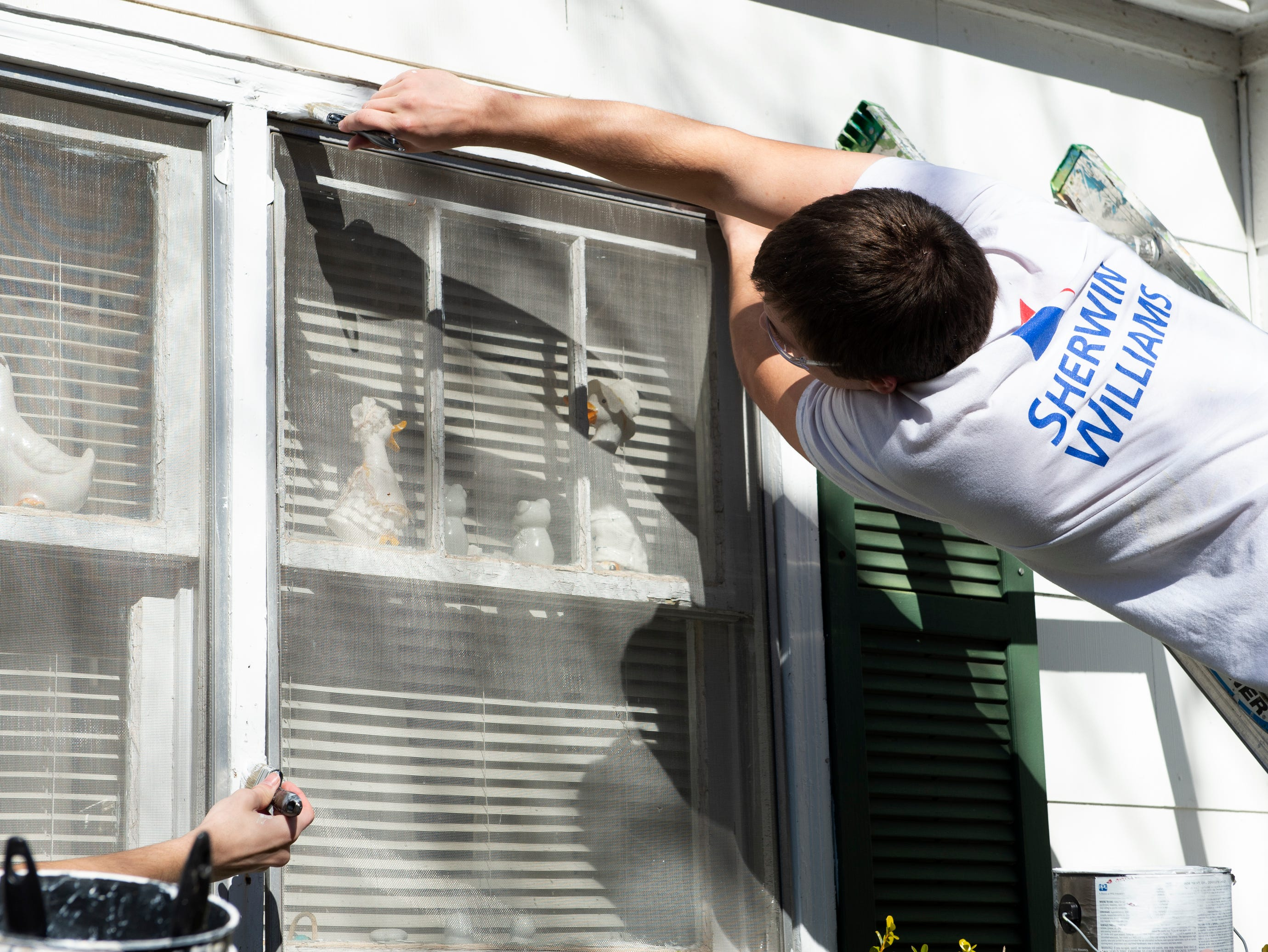 Bob Jones University students paint the windows of a home on Durham Street in Greenville on Martin Luther King, Jr. Day Monday, Jan. 21, 2019.