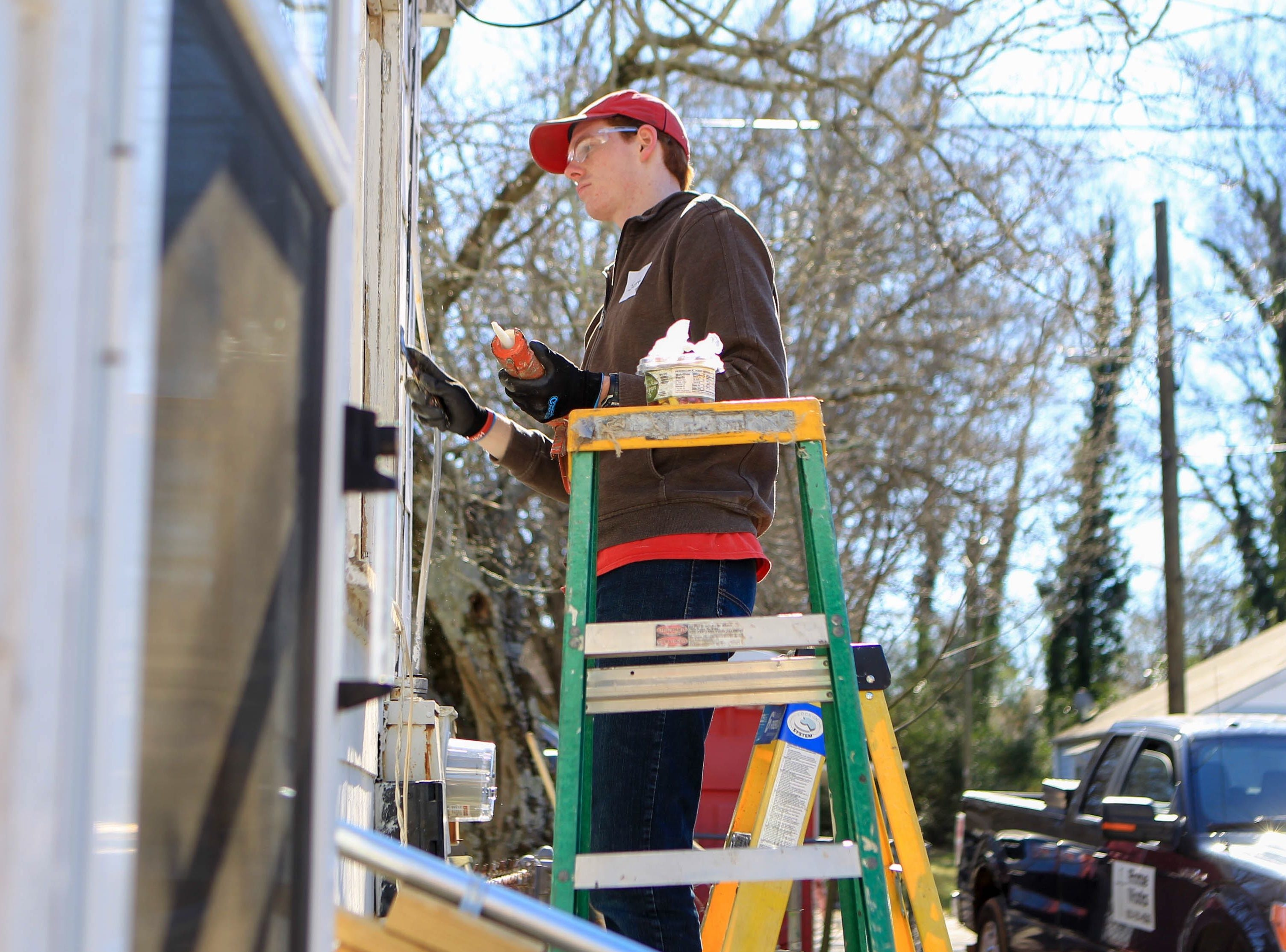 Bob Jones University's Scott Fichter, a junior, works on a home on Durham Street in Greenville on Martin Luther King, Jr. Day Monday, Jan. 21, 2019.