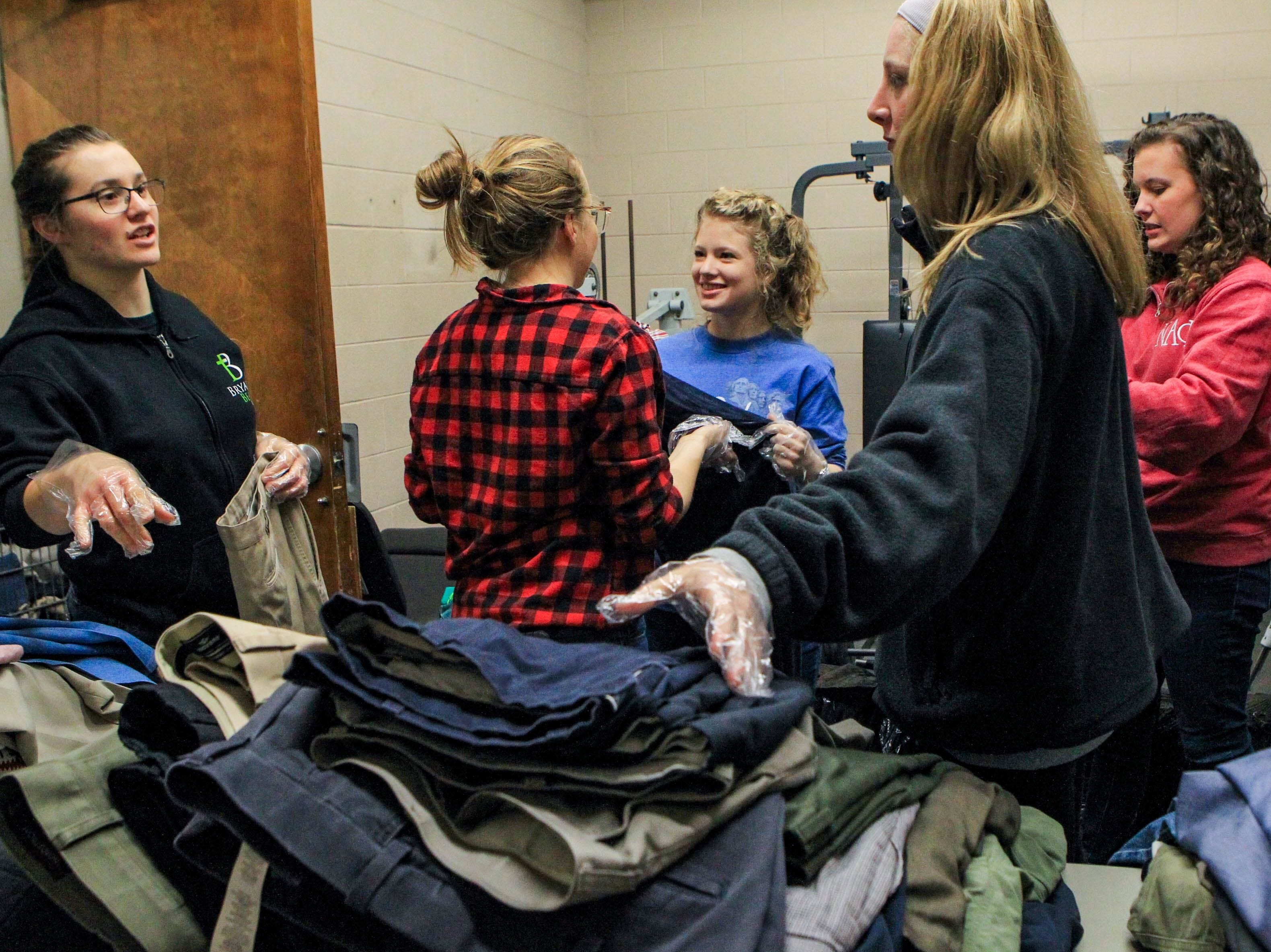 Suzanna Millington, a junior, Taylor Holland, a sophomore, Karen Mee, a sophomore, Sarah Epperson, a senior, and Jennifer Naas, a sophomore, discuss the best way to sort through the pants at Miracle HillÕs Greenville Rescue Mission on Martin Luther King, Jr. Day Monday, Jan. 21, 2019.