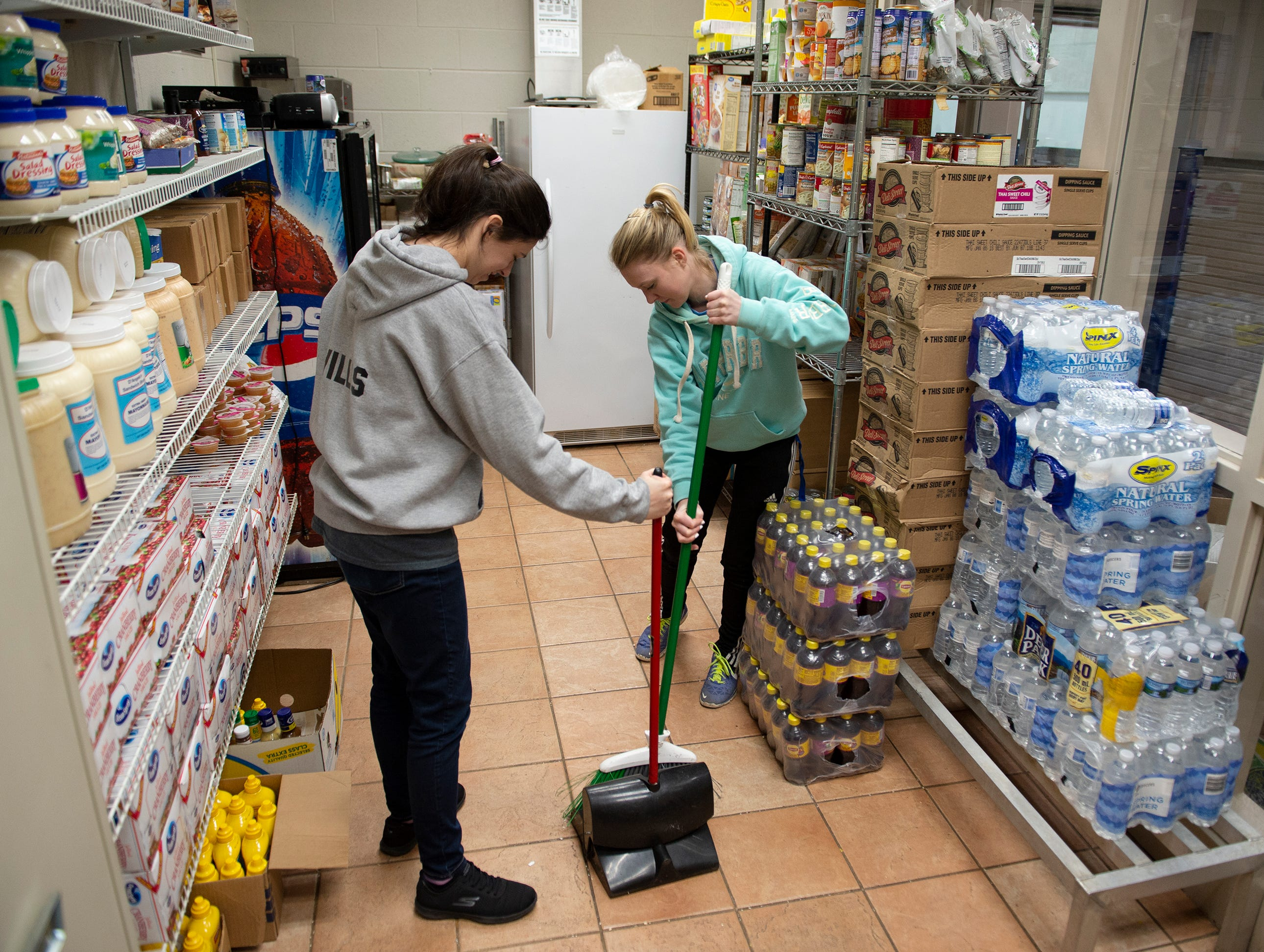 Bob Jones University freshman Kayla Willis (left) and sophomore Jillian Sitton sweep inside Miracle HillÕs Greenville Rescue Mission on Martin Luther King, Jr. Day Monday, Jan. 21, 2019. Twenty volunteers worked at this location while hundreds of students from Bob Jones University volunteered at places around Greenville.