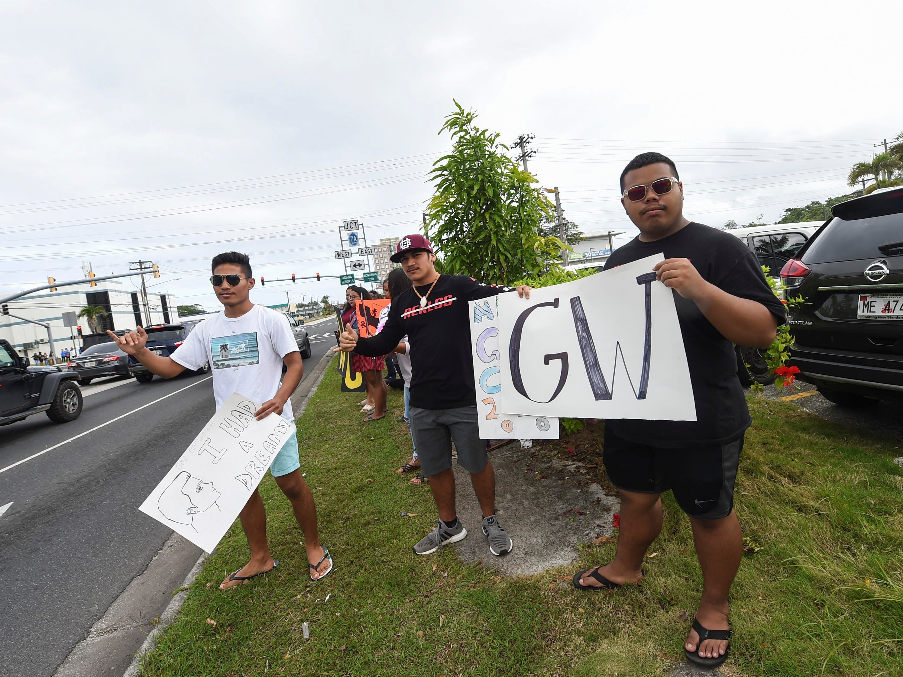 George Washington High School students flash school posters to passing motorists during the 2019 Martin Luther King Jr. Day of Service wave in Hagåtña, Jan. 21, 2019.