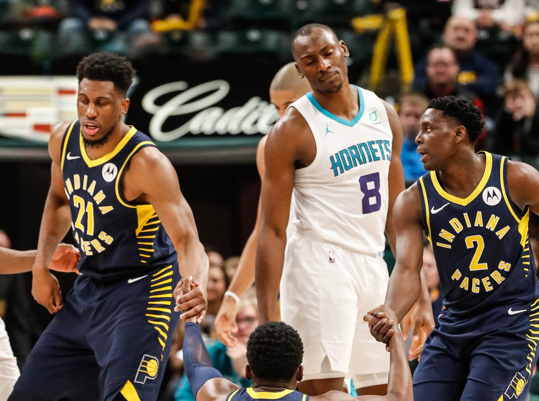 Indiana Pacers guard Victor Oladipo (4) is helped to his feet by team mates Indiana Pacers forward Thaddeus Young (21), and Indiana Pacers guard Darren Collison (2), as Charlotte Hornets center Bismack Biyombo (8) reacts, during a game between the Pacers and Hornets at Bankers Life Fieldhouse on Sunday, Jan. 20, 2019.
